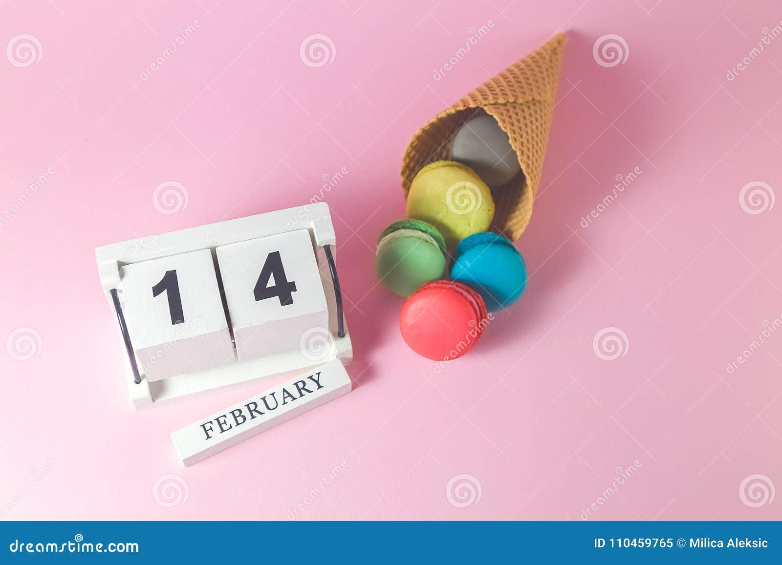Färgrika macarons i glasskotte med träkalendern