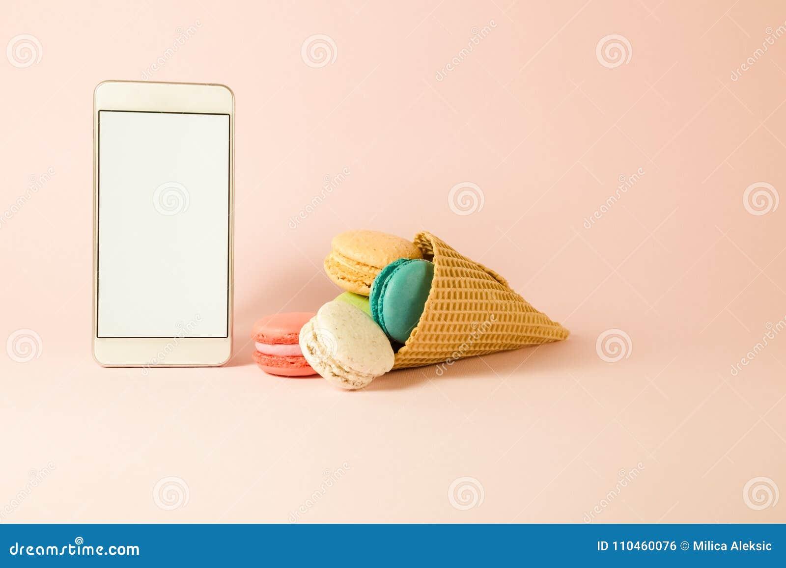 Färgrika macarons i glasskotte och smartphone med den tomma skärmen