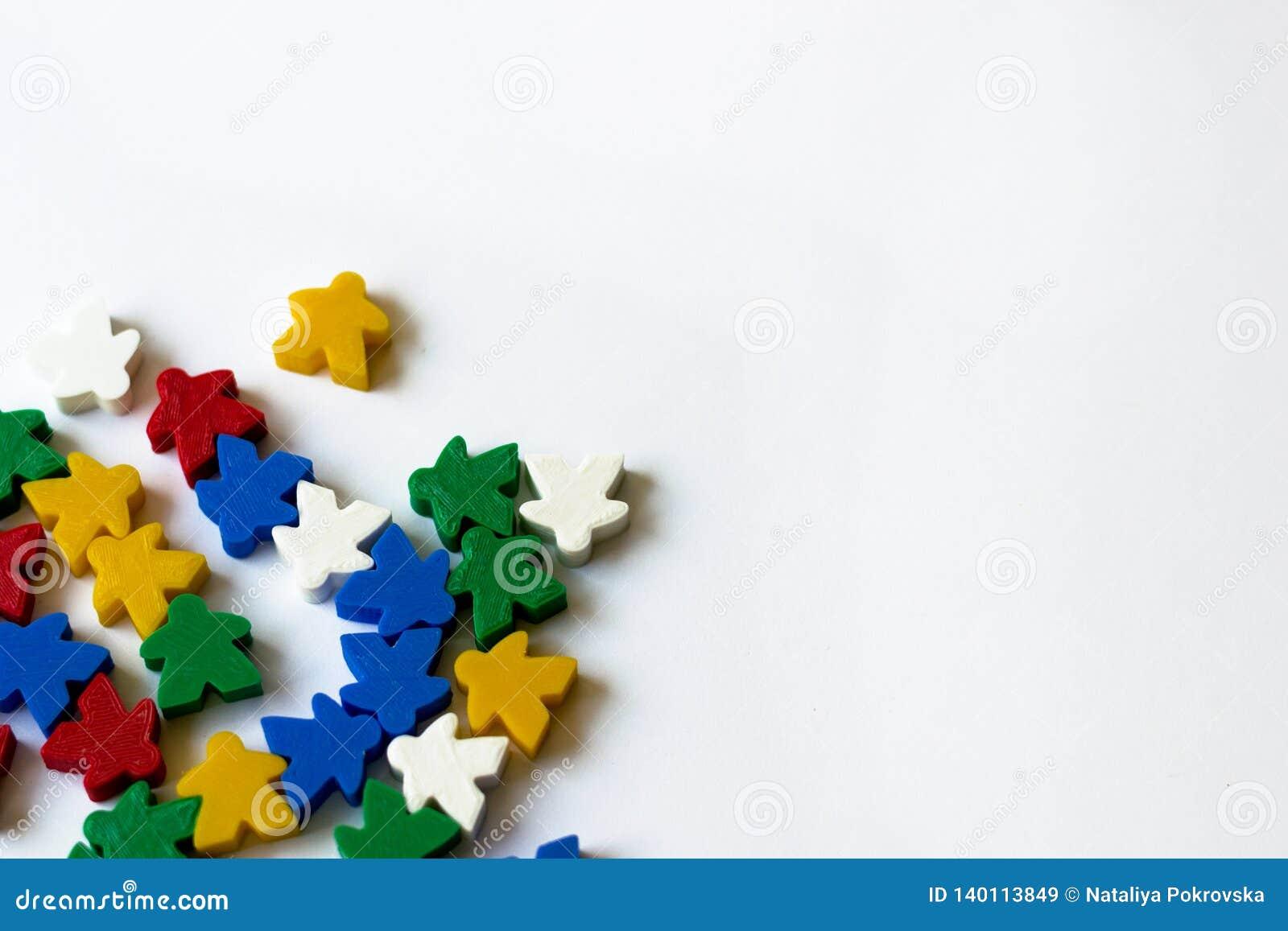 Färgrika meeples som delar av brädeleken på vit bakgrund med copyspace Begrepp av sällskapsspelet som spelar, fritid, gyckel,
