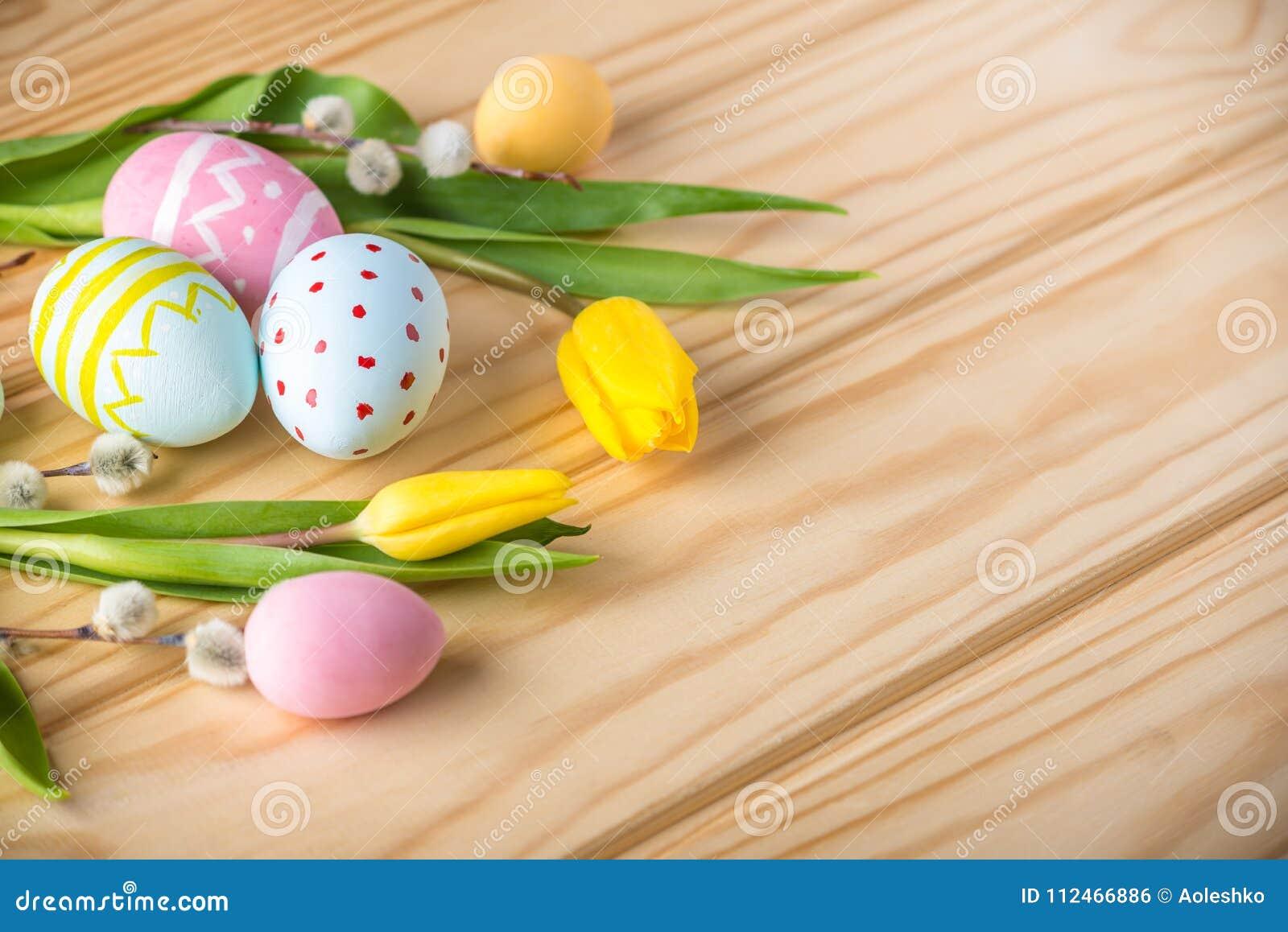 Färgrika påskägg med den gula tulpanhanden målade på en ljus träbakgrund Festligt vårkort