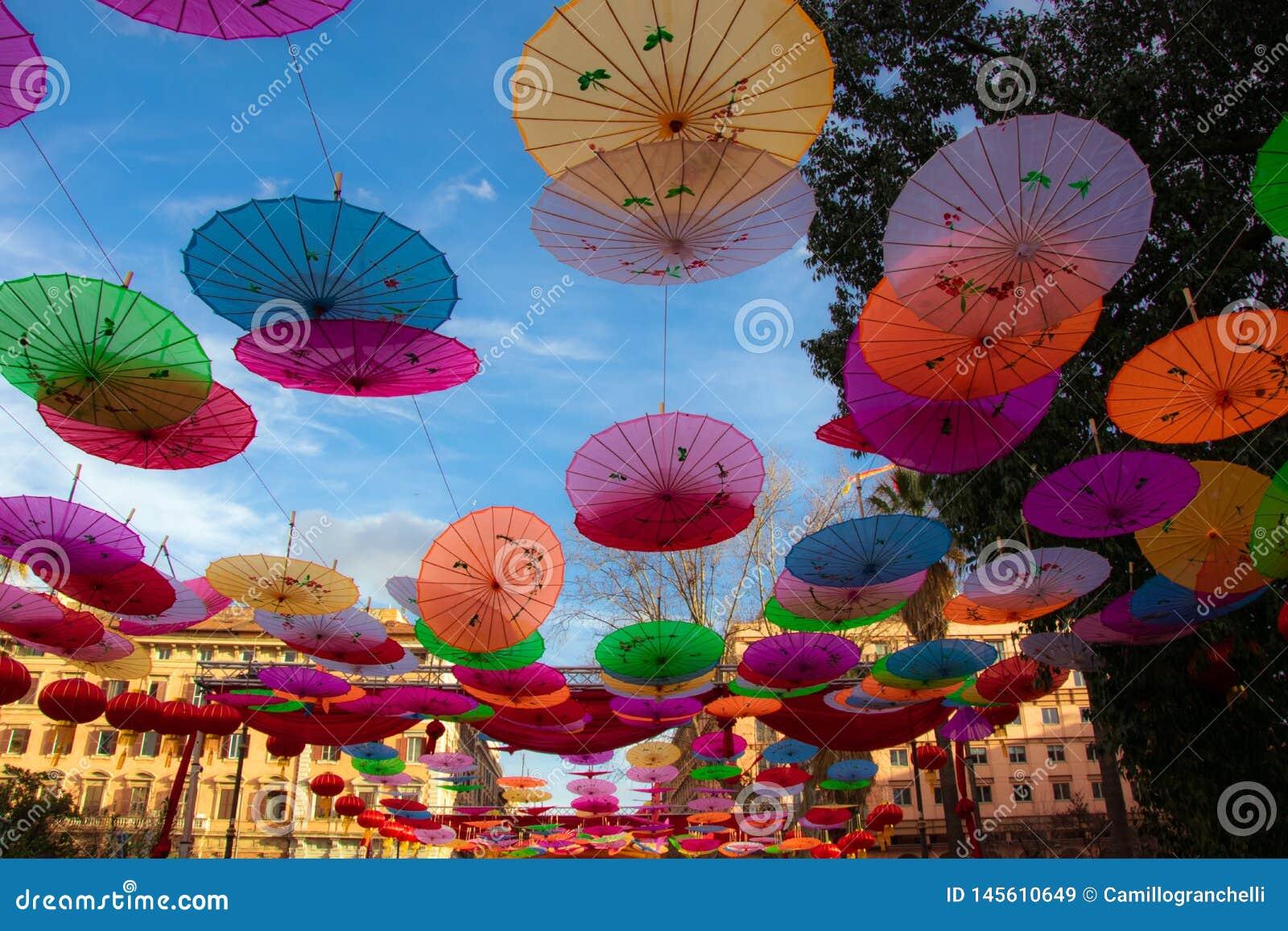 Färgrika pappers- paraplyer på himmelbakgrunden