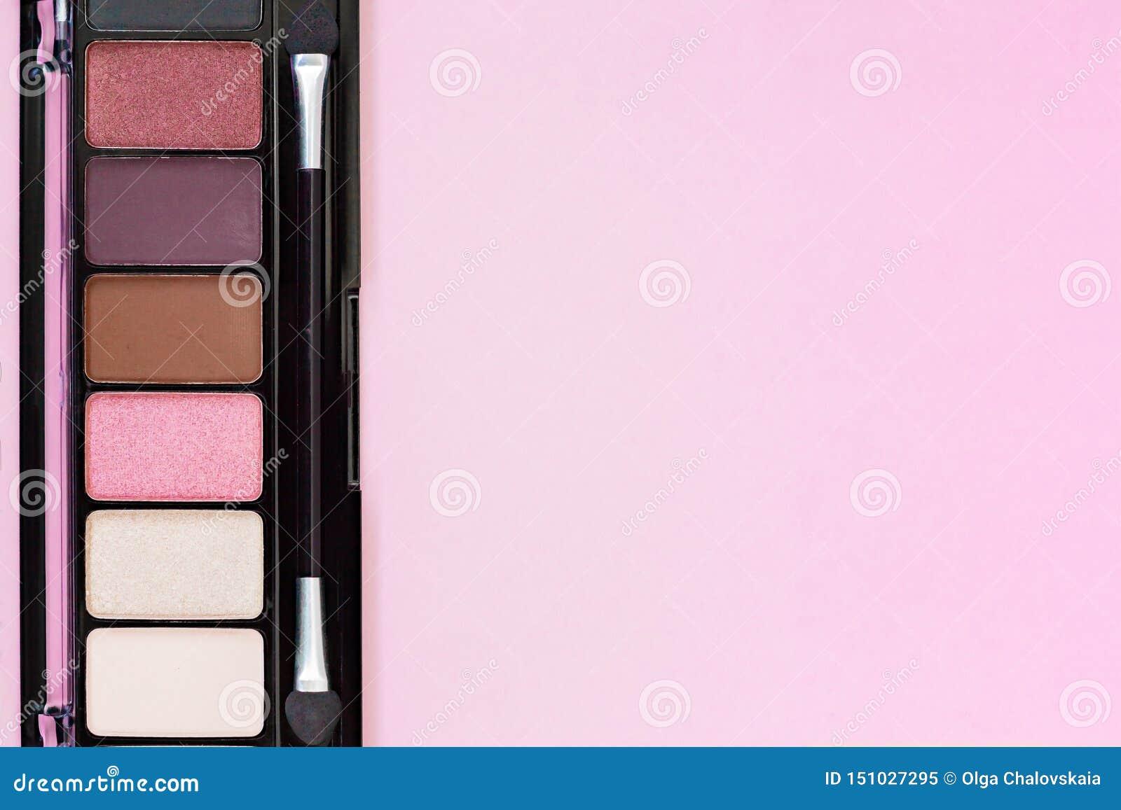 Färgrika produkter för makeup för palett för ögonskugga på pastellfärgad rosa bakgrund med kopieringsutrymme
