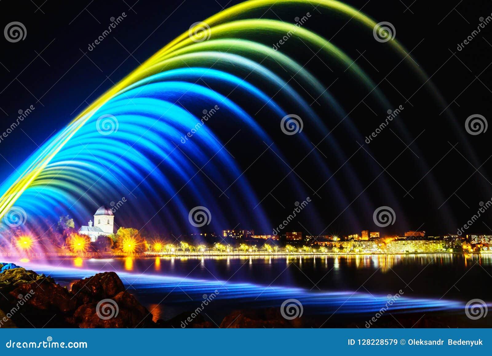 Färgrika springbrunnar i stad parkerar på nattetid, lång exponeringspho