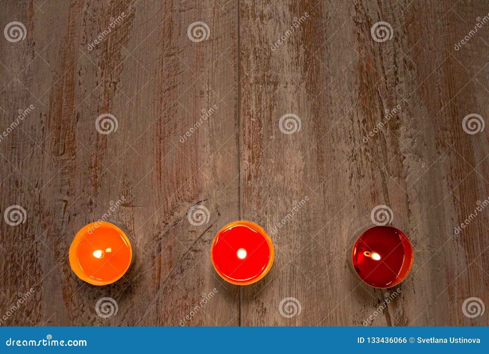 Färgrika stearinljus på träbrädena