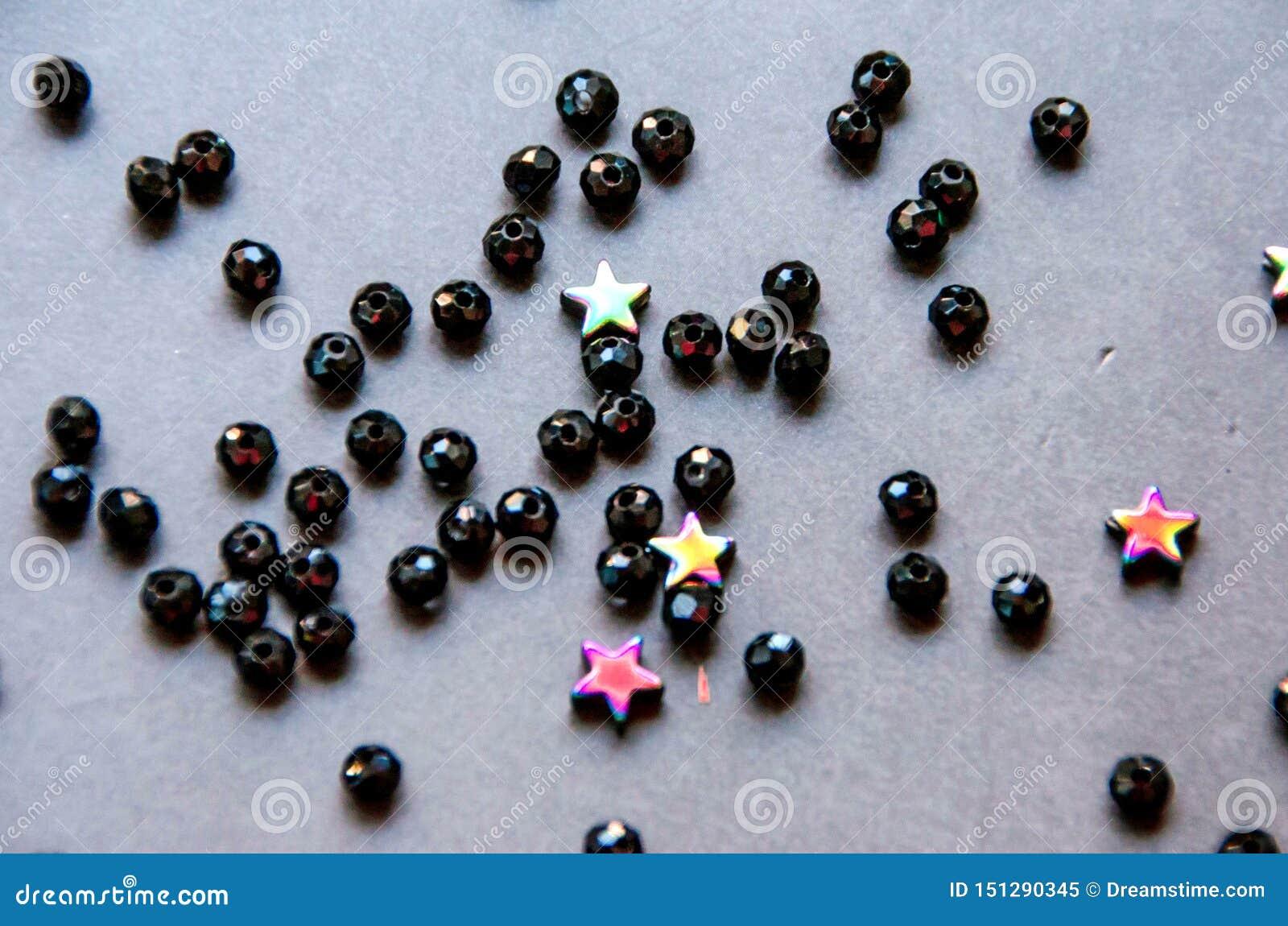 Färgrika svarta pärlor och stenar isolerade grå bakgrund