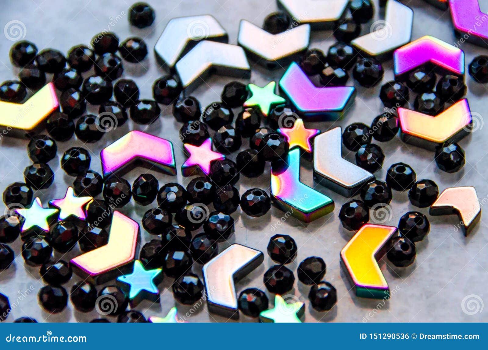 Färgrika svarta pärlor och stenar som isoleras på grå bakgrund