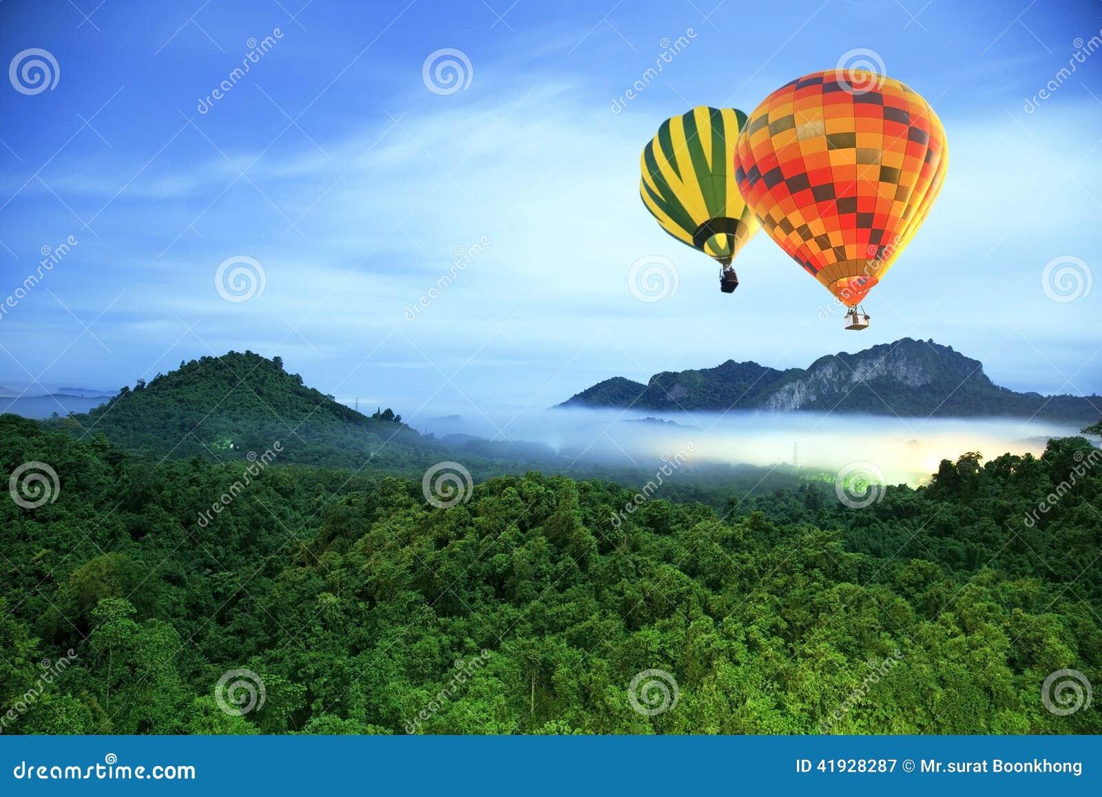 Färgrika varmluftsballonger som flyger över berget