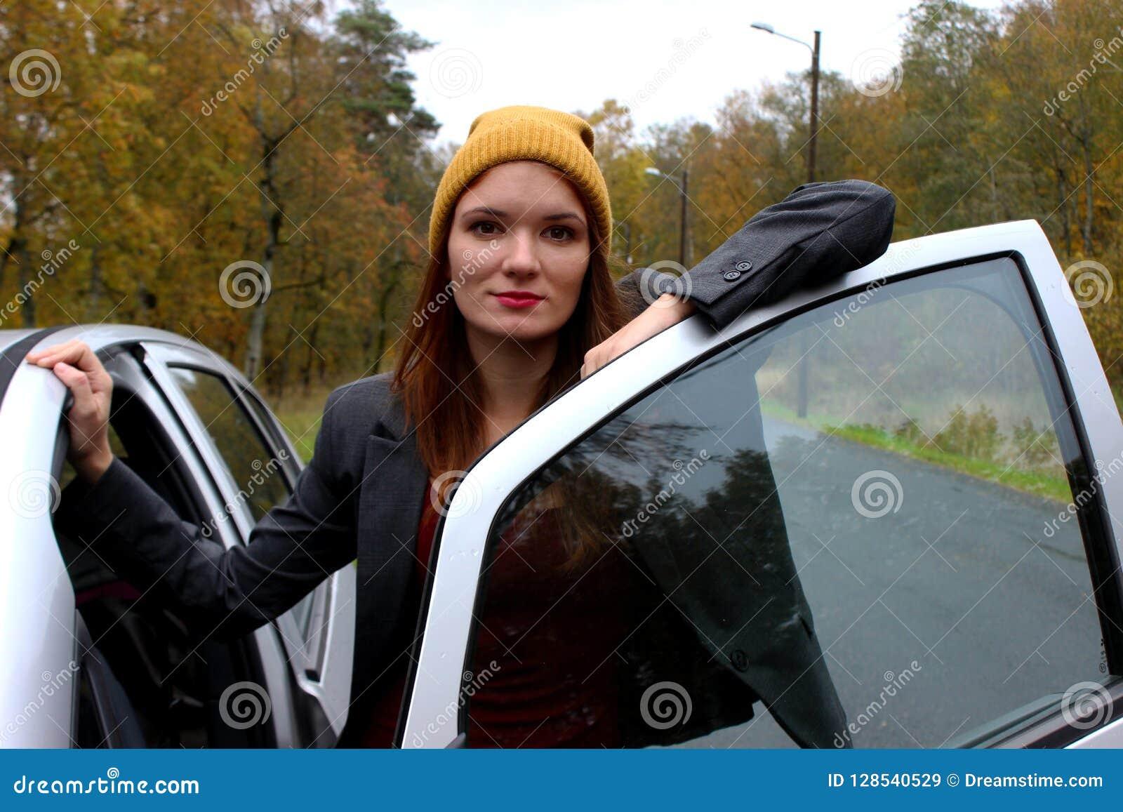 Få klart Stående av den unga le damen som står den near bil- och öppningsdörren