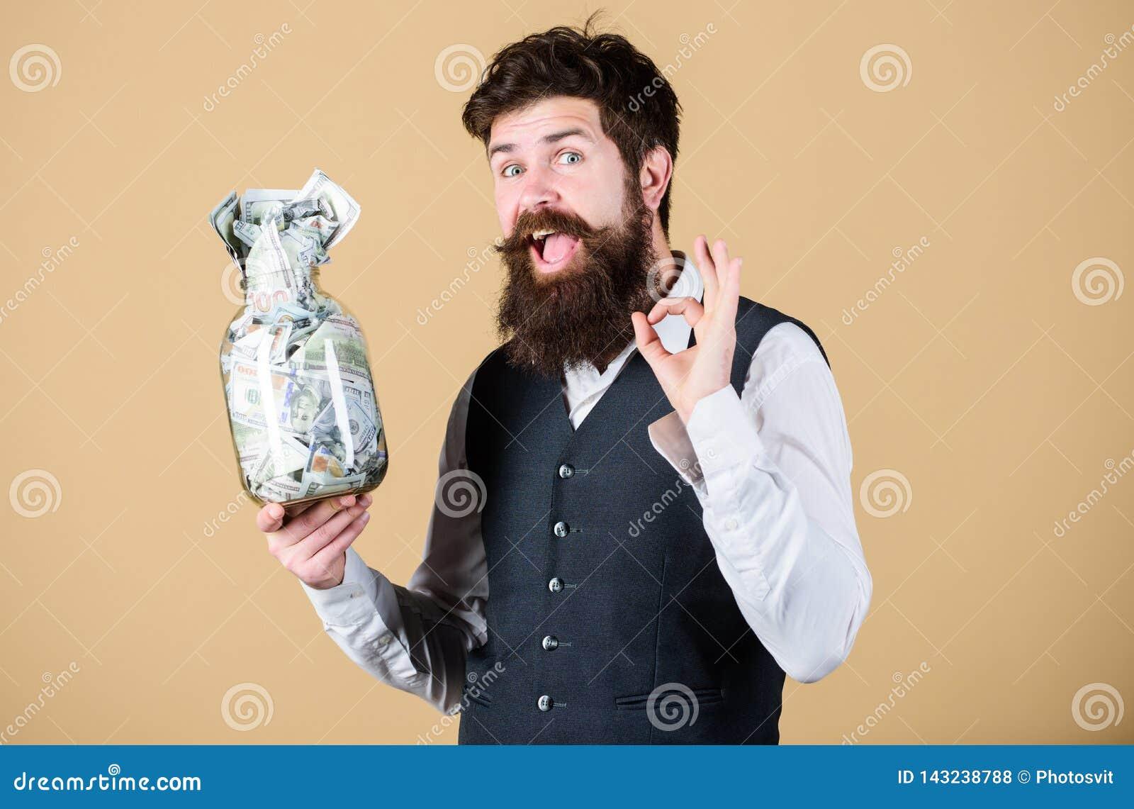 Få rikt Rikt göra en gest för affärsman som är ok med pengar i exponeringsglaskrus Skäggig rikeman med pengarkassa När blivet a
