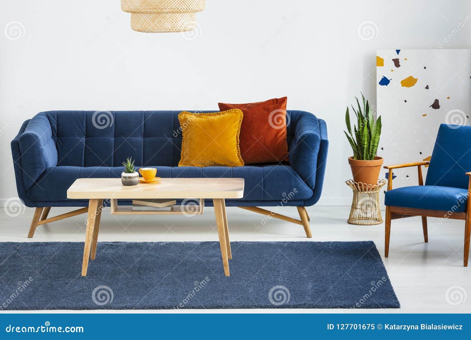 Fåtölj bredvid den blåa soffan med kuddar och trätabellen i plan inre med växten Verkligt foto