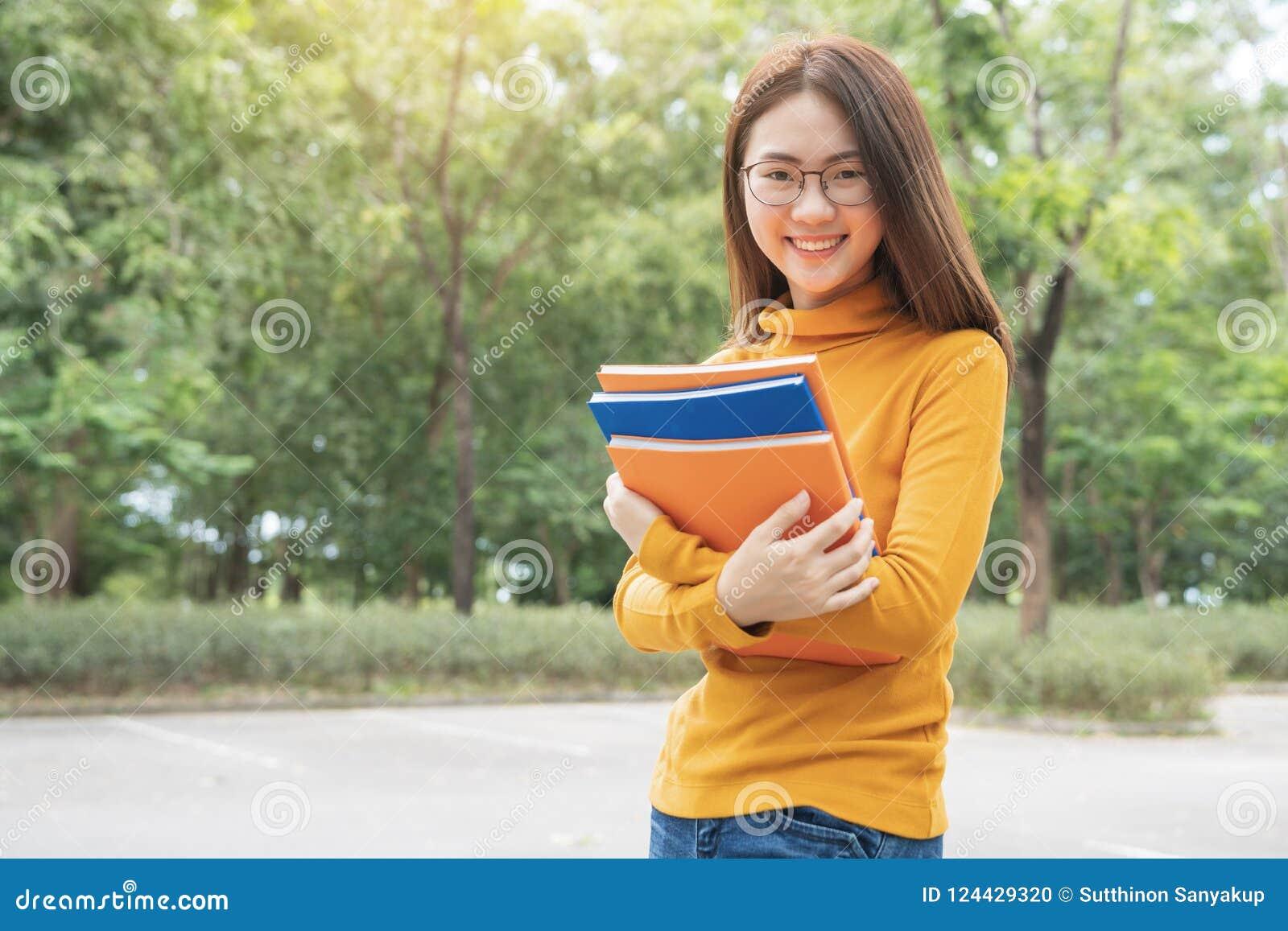Férias de verão, educação, terreno e conceito adolescente - estudante fêmea de sorriso em monóculos pretos com dobradores e grupo