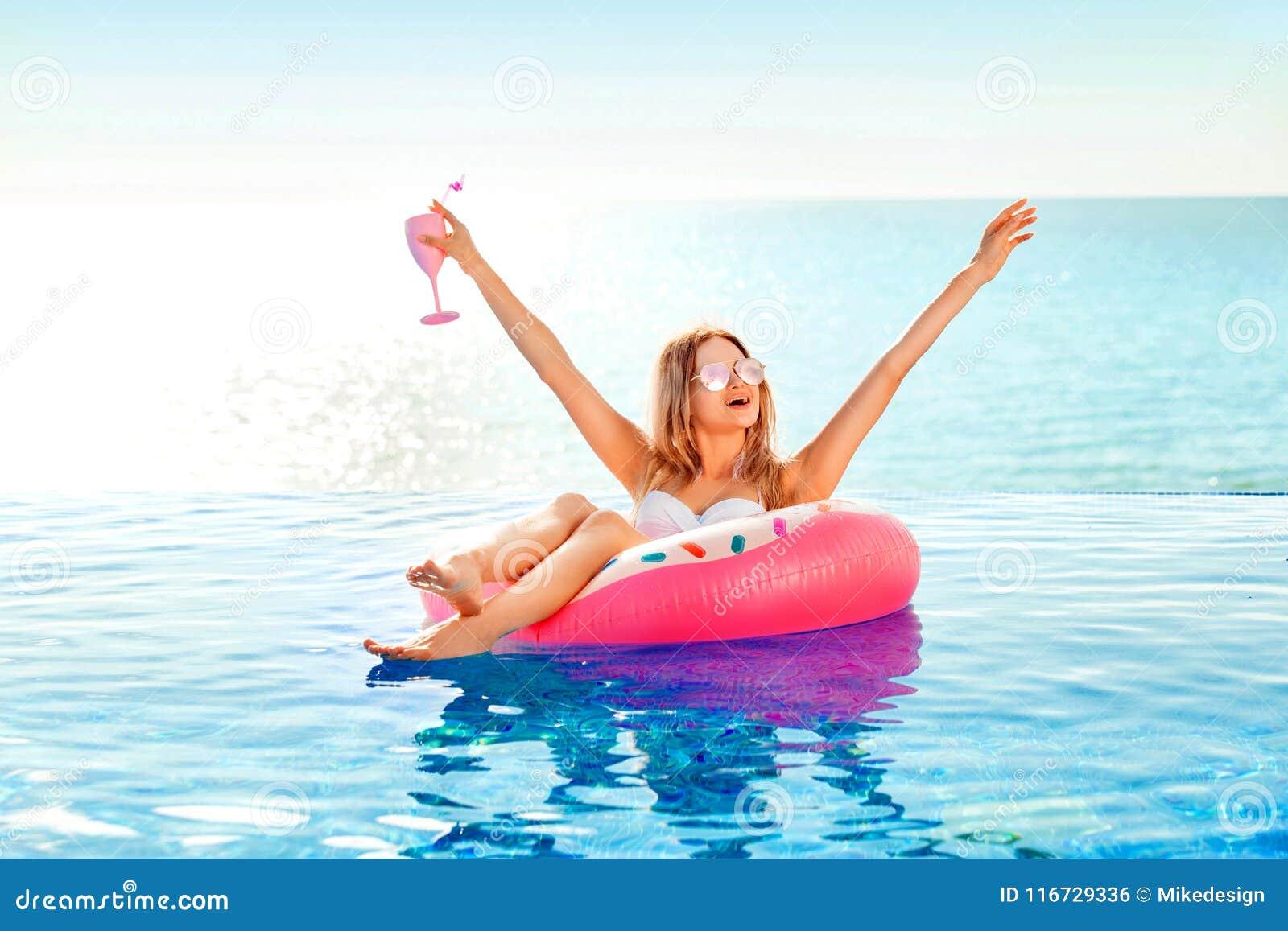 Férias de verão Mulher no biquini no colchão inflável da filhós na piscina dos TERMAS