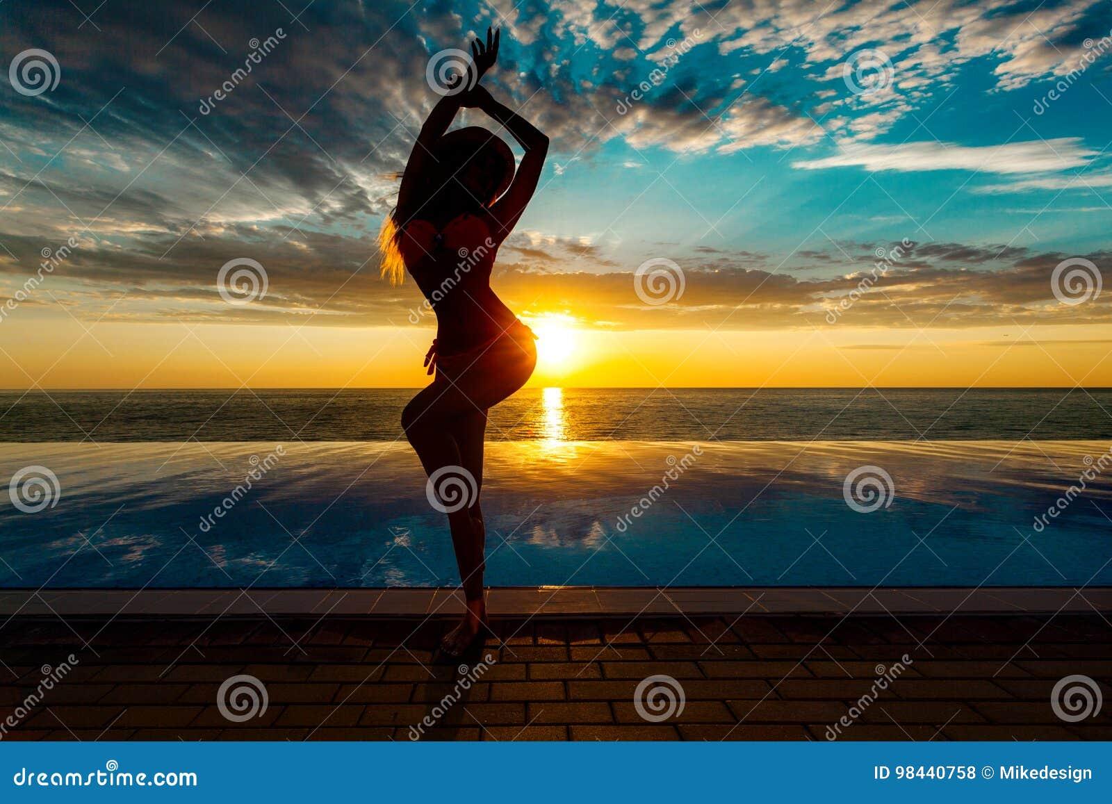 Férias de verão Silhueta da mulher da dança da beleza no por do sol perto da associação com vista para o mar
