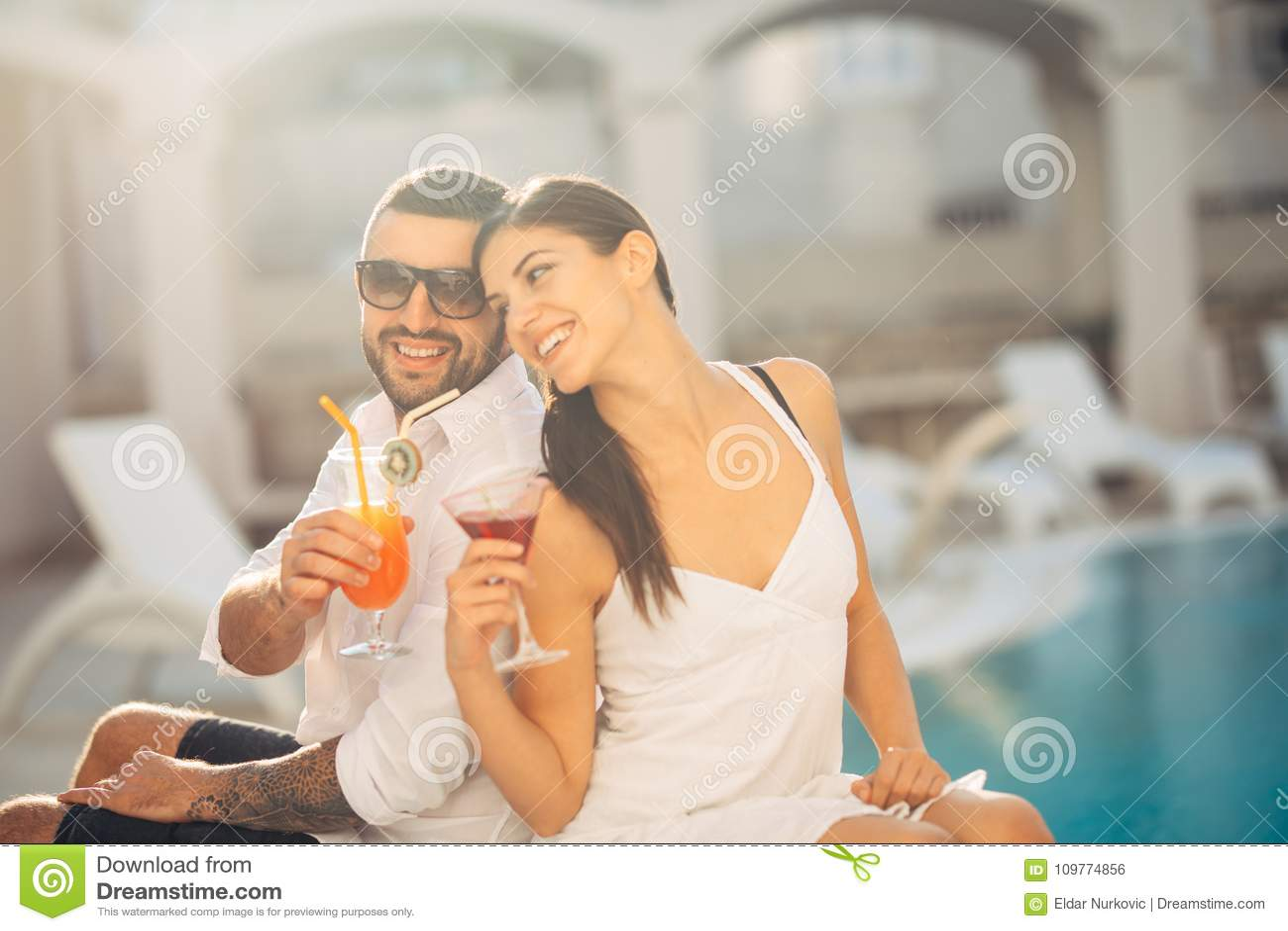 Férias loving da despesa dos pares na piscina tropical do recurso Lua de mel dos recém-casados no beira-mar