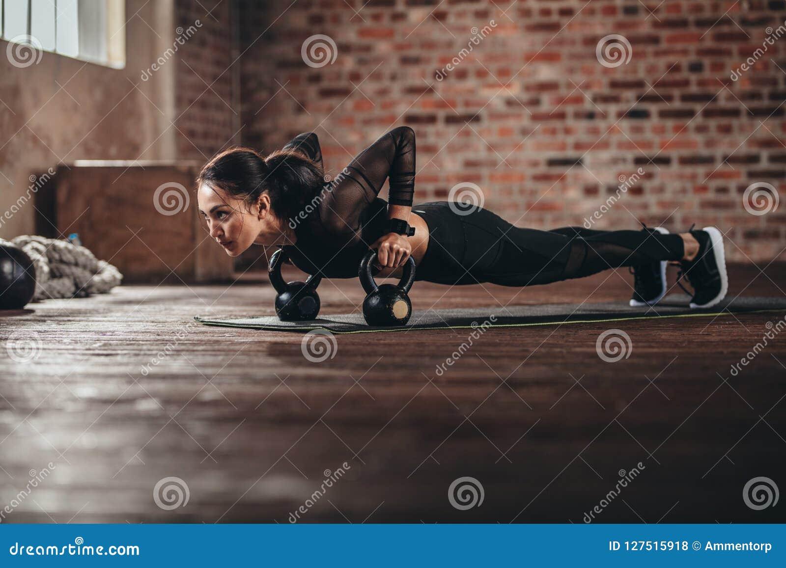 Fêmea apta que faz o exercício intenso do núcleo no gym