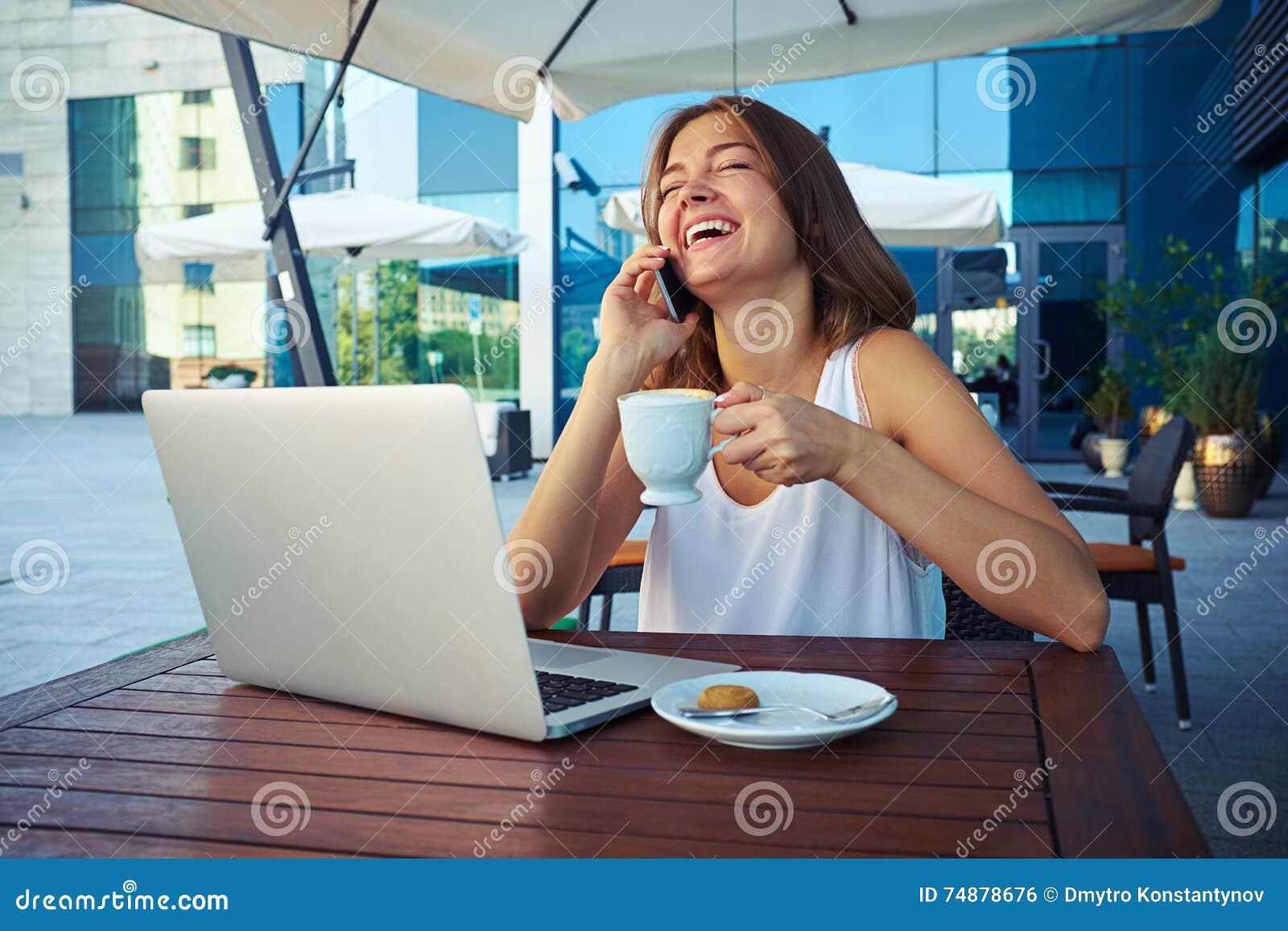 Fêmea atrativa com xícara de café que ri ao falar em t