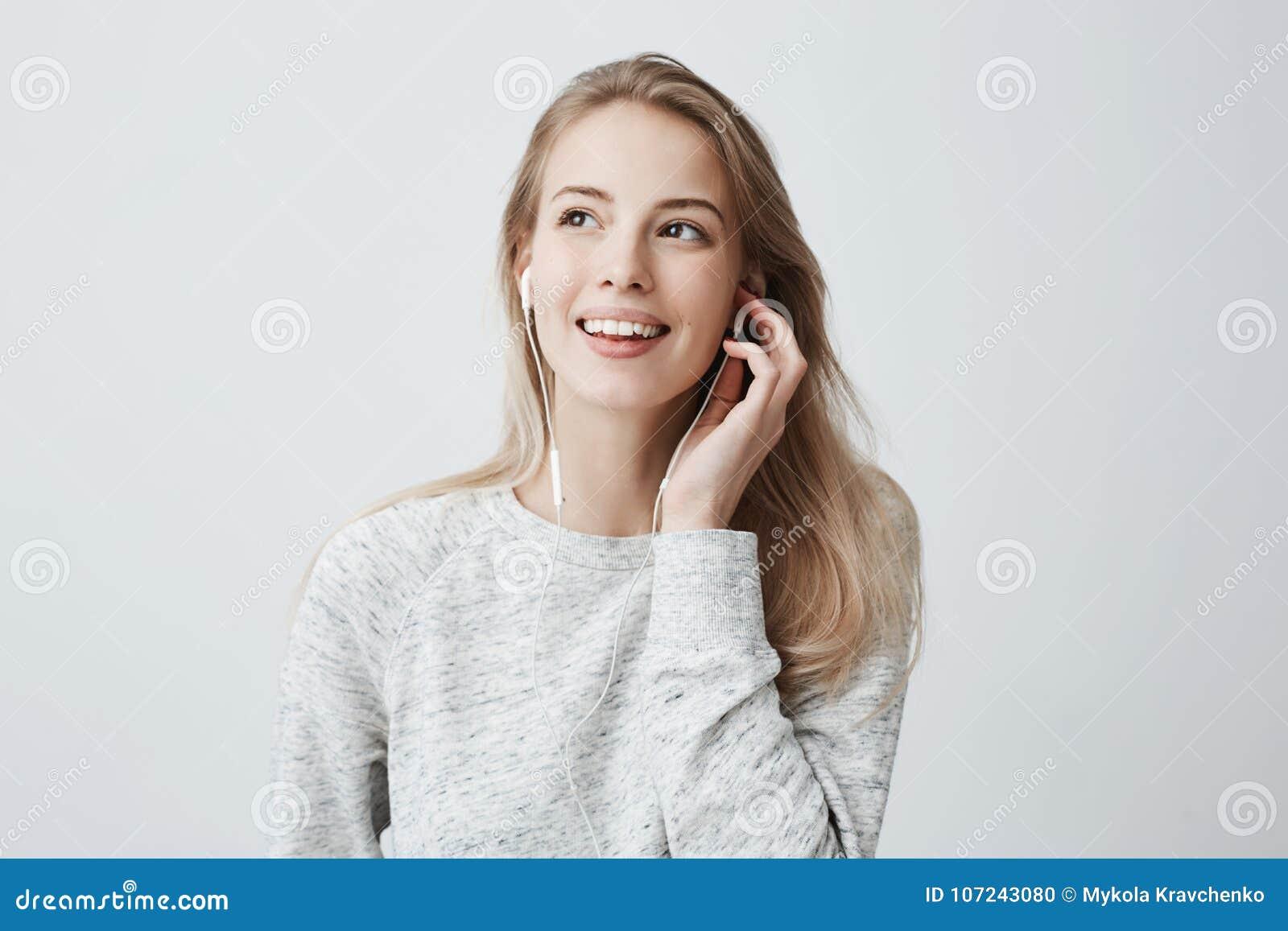 A fêmea caucasiano nova feliz expressivo veste o cabelo tingido louro frouxamente, escuta a música nos fones de ouvido, aprecia a
