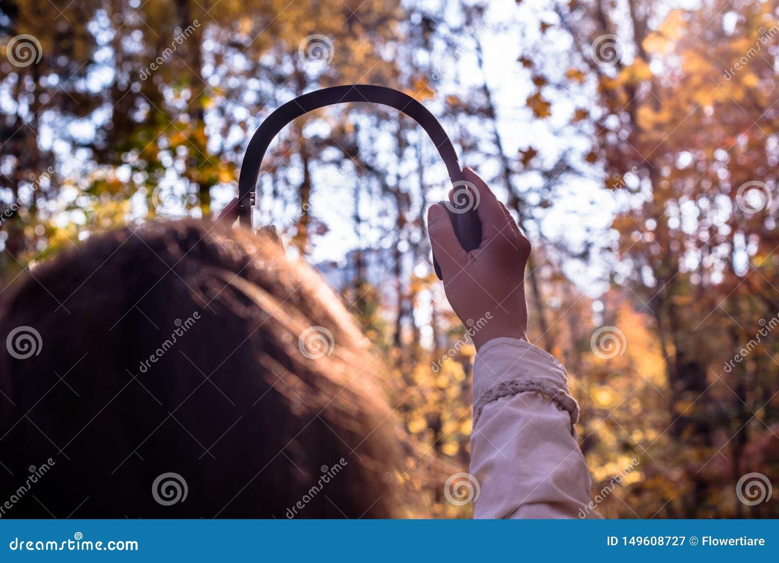 A fêmea com fones de ouvido que anda no parque escuta sons ou música do conceito da floresta do outono Temporada de ver?o indiana
