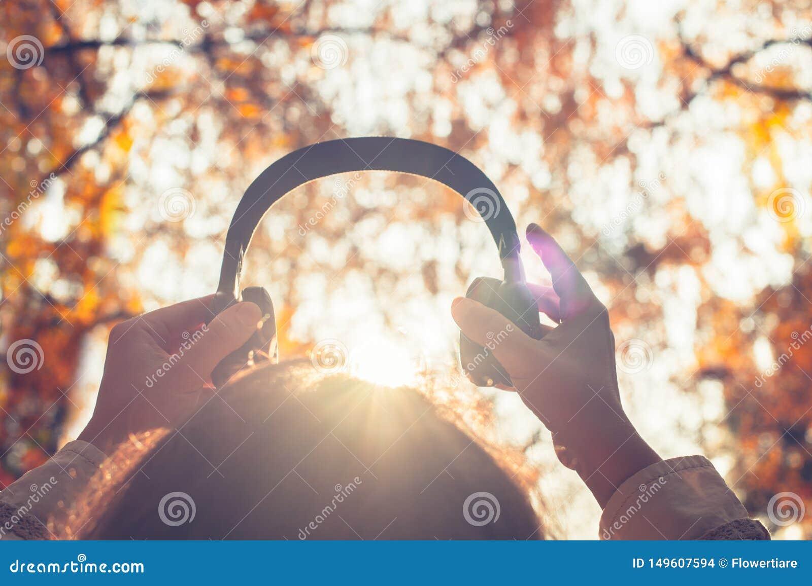 A fêmea com fones de ouvido que anda no parque escuta sons ou música do conceito da floresta do outono Ver?o indiano