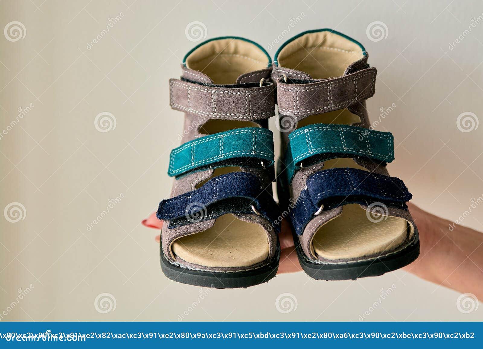 A fêmea está mantendo o close-up sandálias da sapata ortopédica de umas crianças especiais feito do couro genuíno