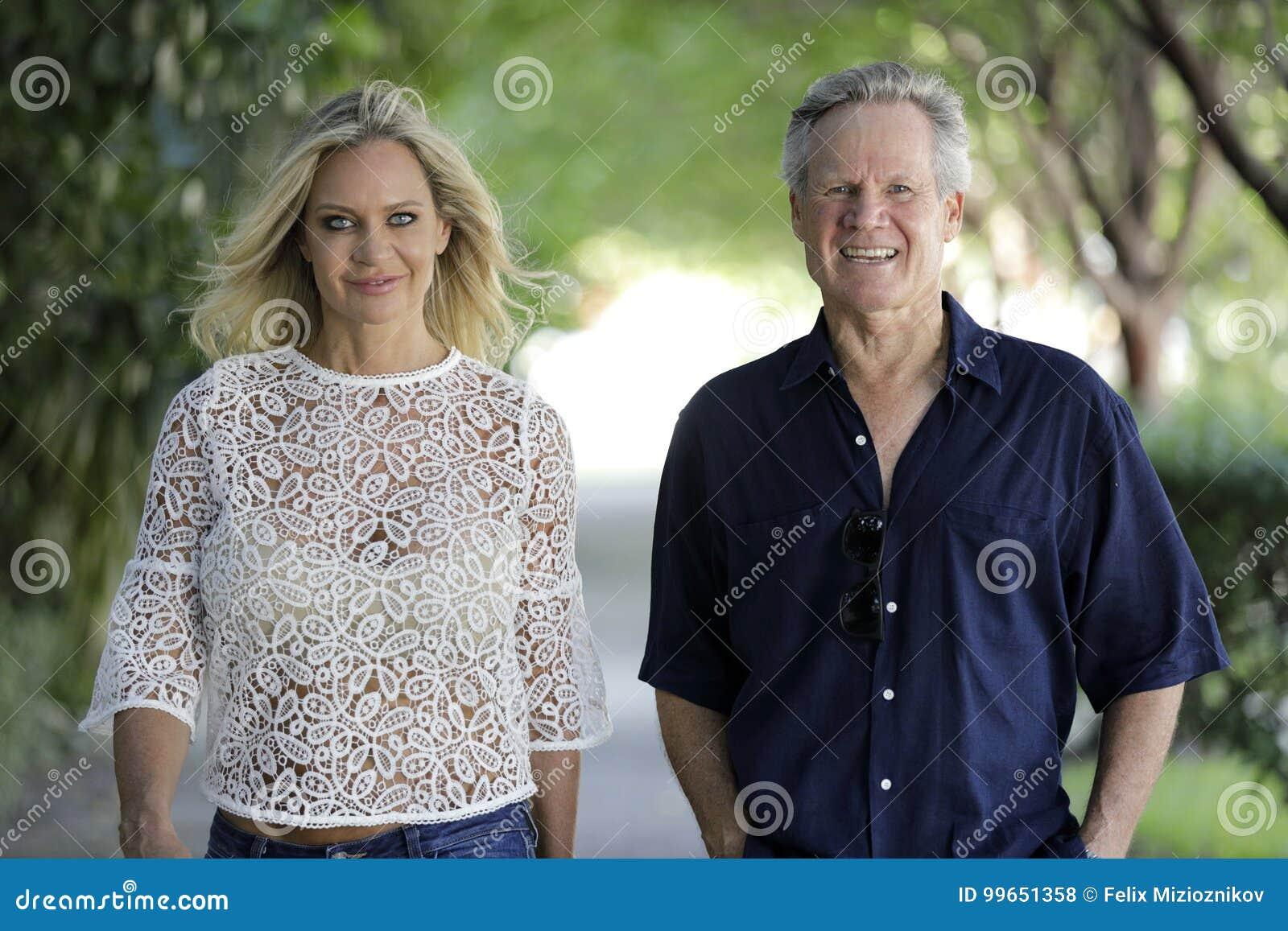 Fêmea loura atrativa com um homem mais idoso