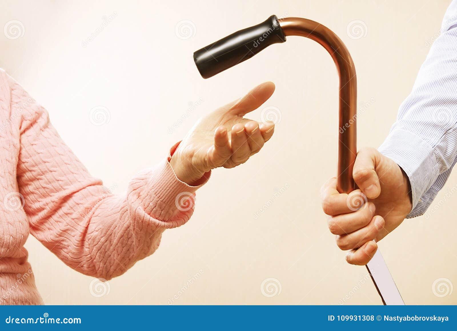 A fêmea madura em instalações de cuidados idosas obtém a ajuda da enfermeira dos pessoais do hospital Feche acima das mãos enruga