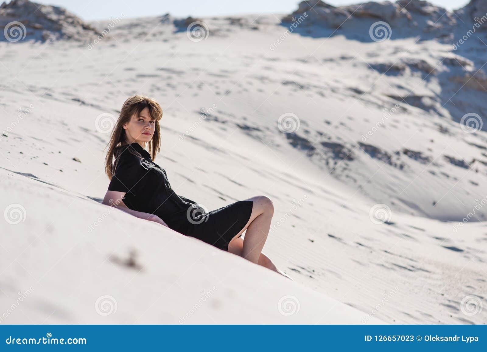 Fêmea nova atrativa colocada em dunas do deserto