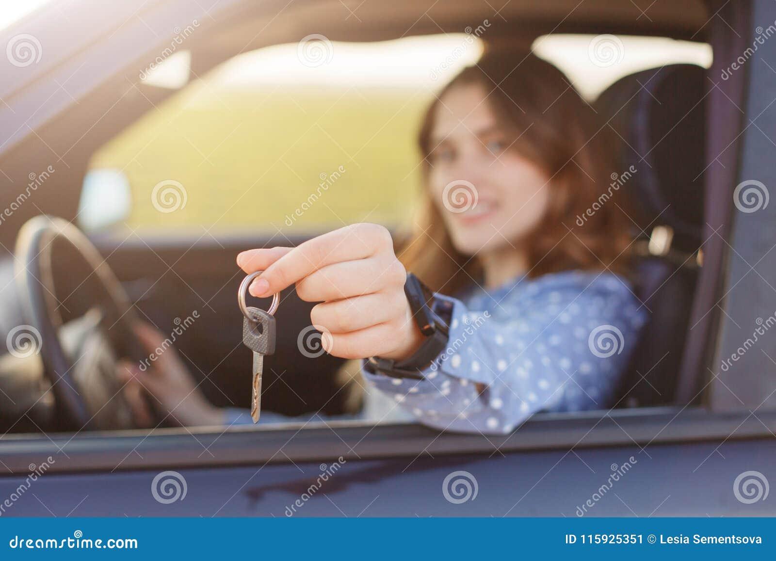 A fêmea nova atrativa guarda chaves do carro, sendo proprietário feliz do automóvel novo, fundo borrado A mulher bonita vende o v
