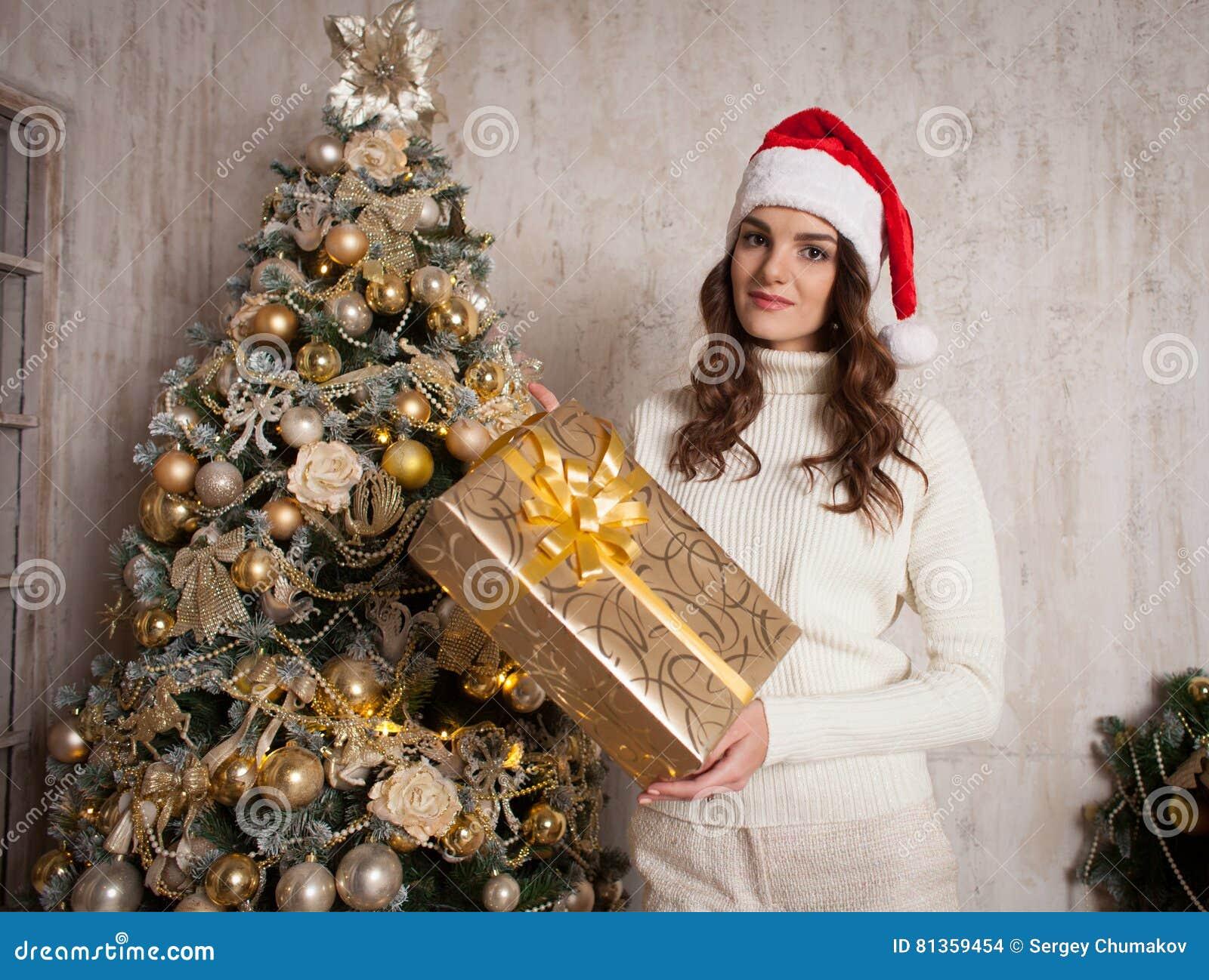 Fêmea nova com a caixa de presente perto da árvore de Natal na casa do cosiness