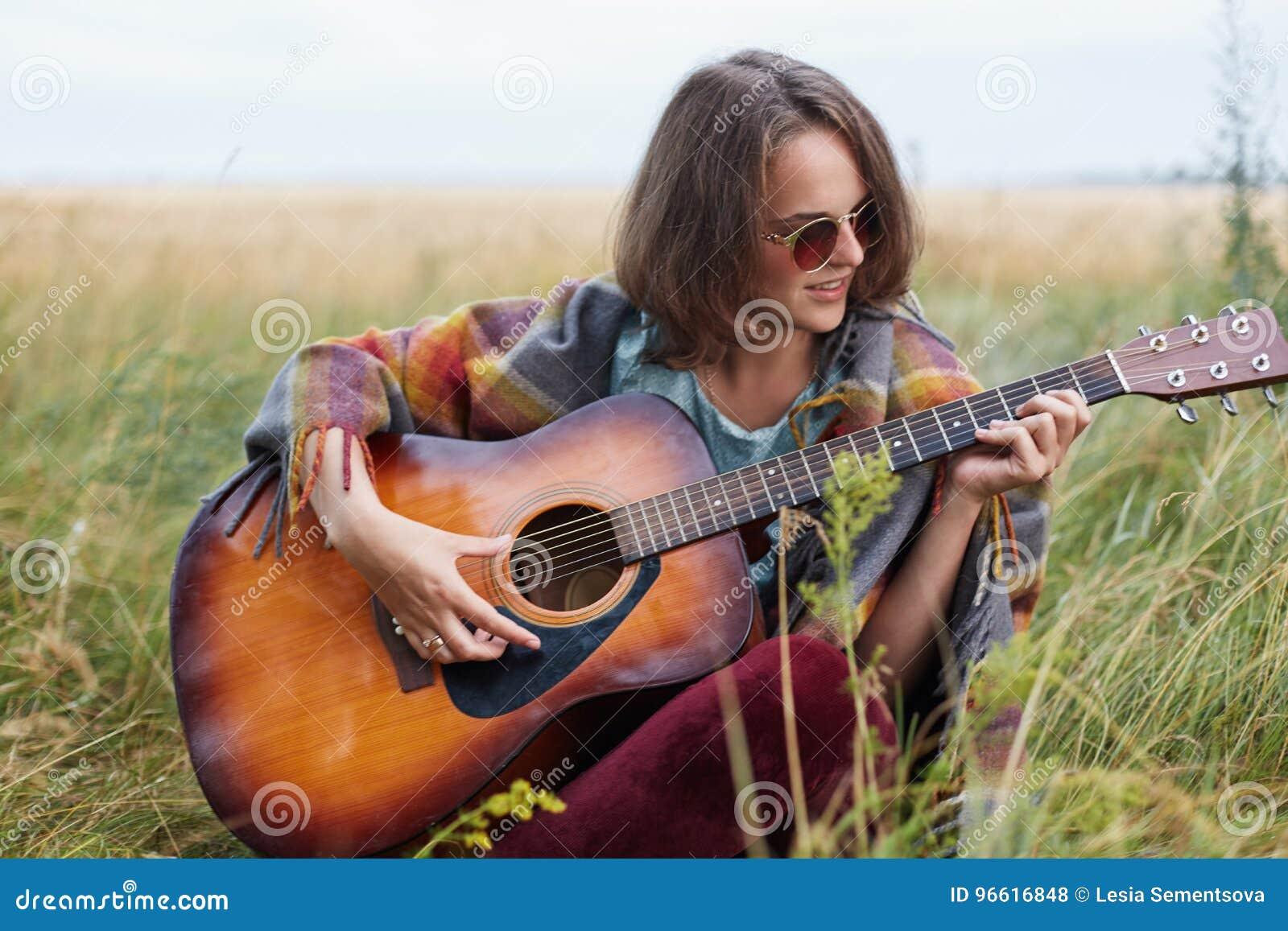Fêmea nova com o cabelo curto escuro que senta-se na grama verde que joga fora a guitarra que aprecia paisagens agradáveis que ca