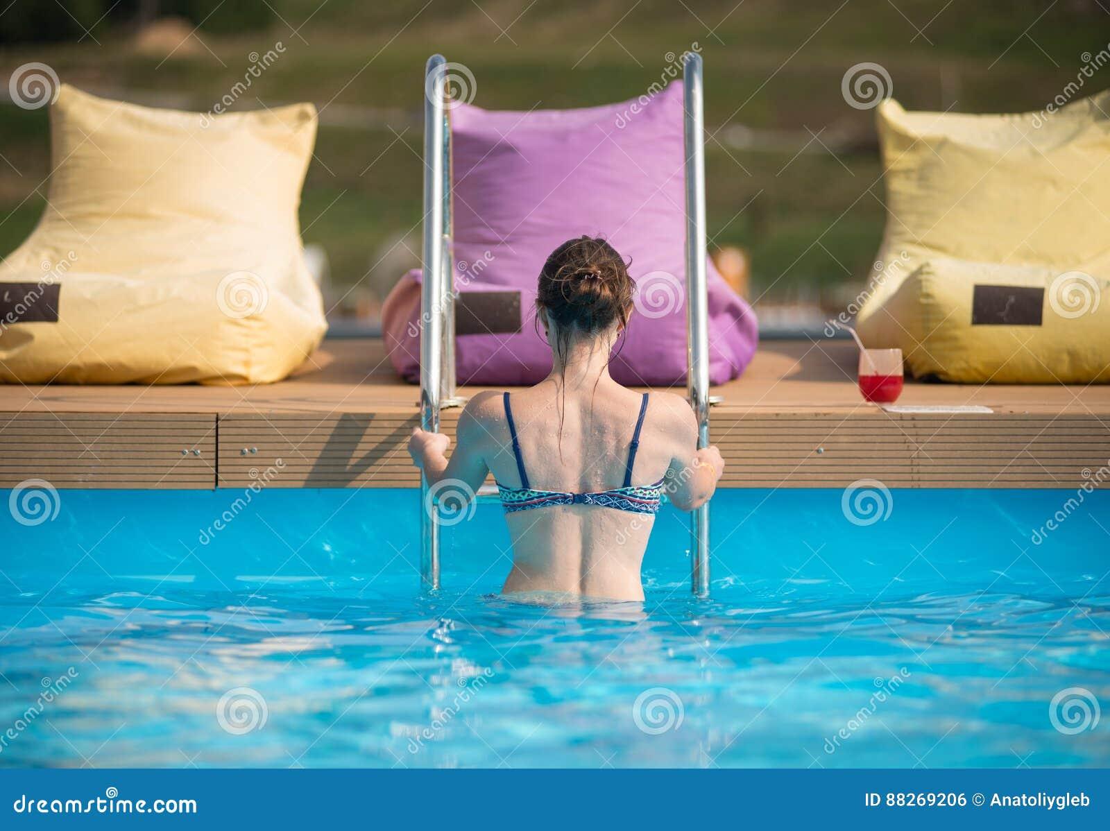 Fêmea nova da vista traseira no roupa de banho que sai da água de uma piscina no recurso