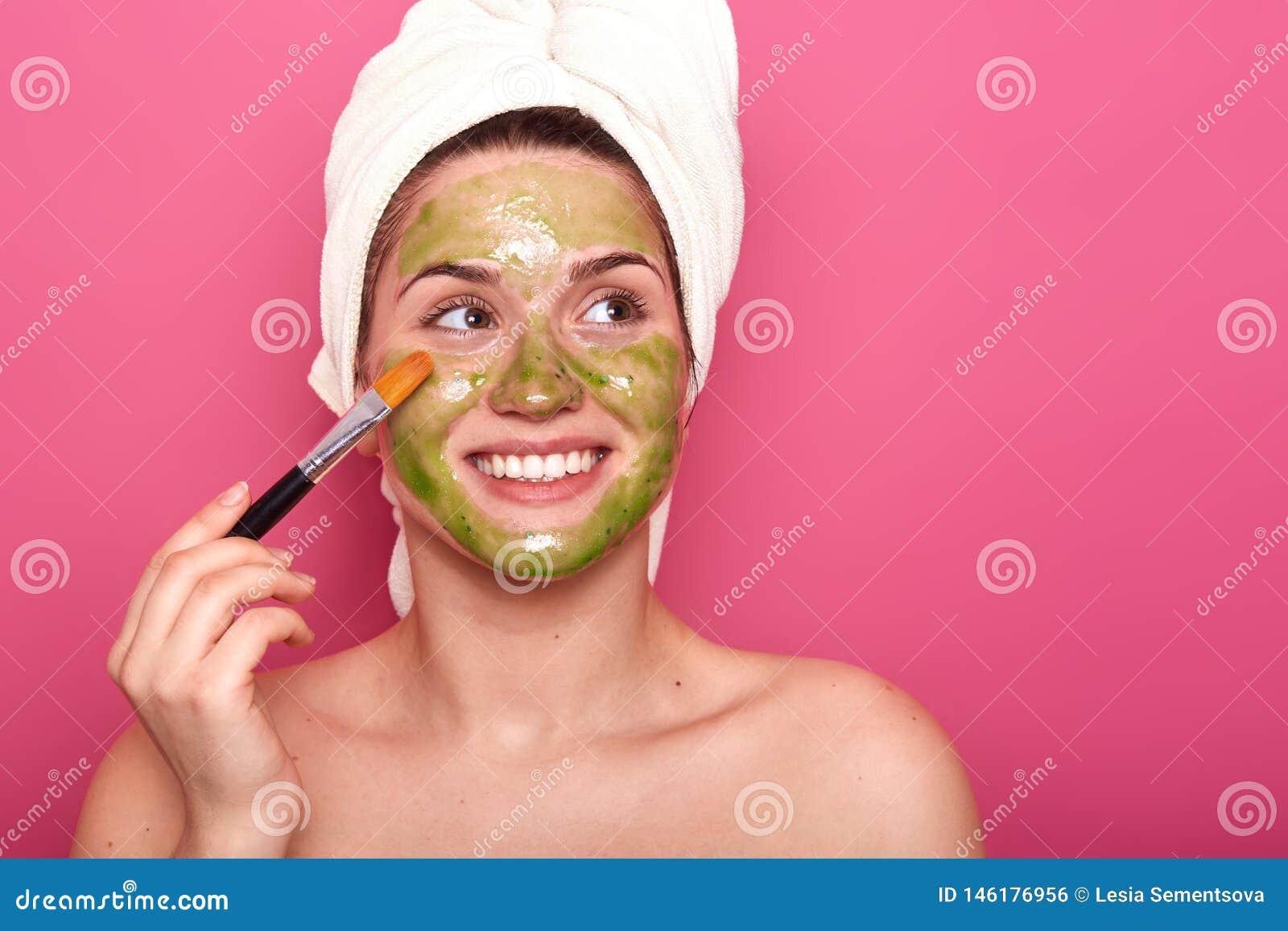 Fêmea nova positiva alegre que põe a máscara colorida sobre sua cara com ajuda da escova profissional, olhando de lado, estando f