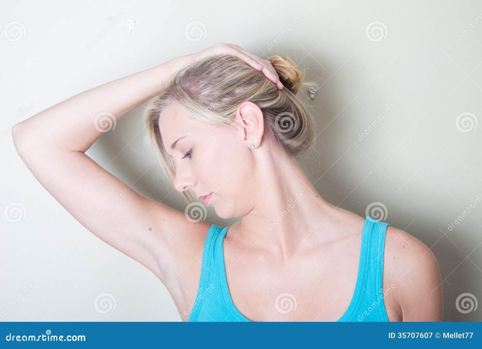 Fêmea nova que usa exercícios de pescoço das mãos