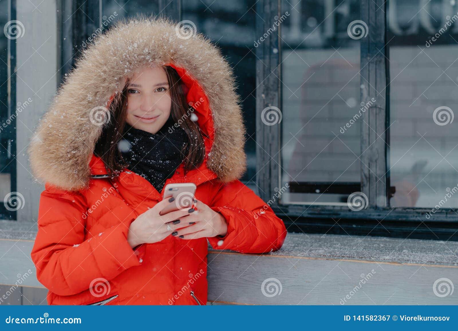 A fêmea parecendo jovem agradável no revestimento vermelho, guarda o telefone esperto moderno, conta bancária das verificações, e