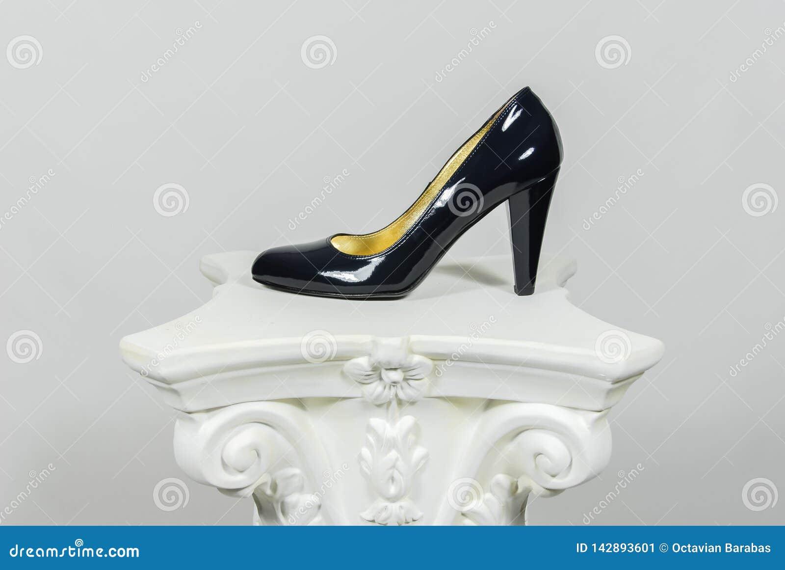 A fêmea preta elegante alto-colocou saltos a sapata de couro na coluna grega