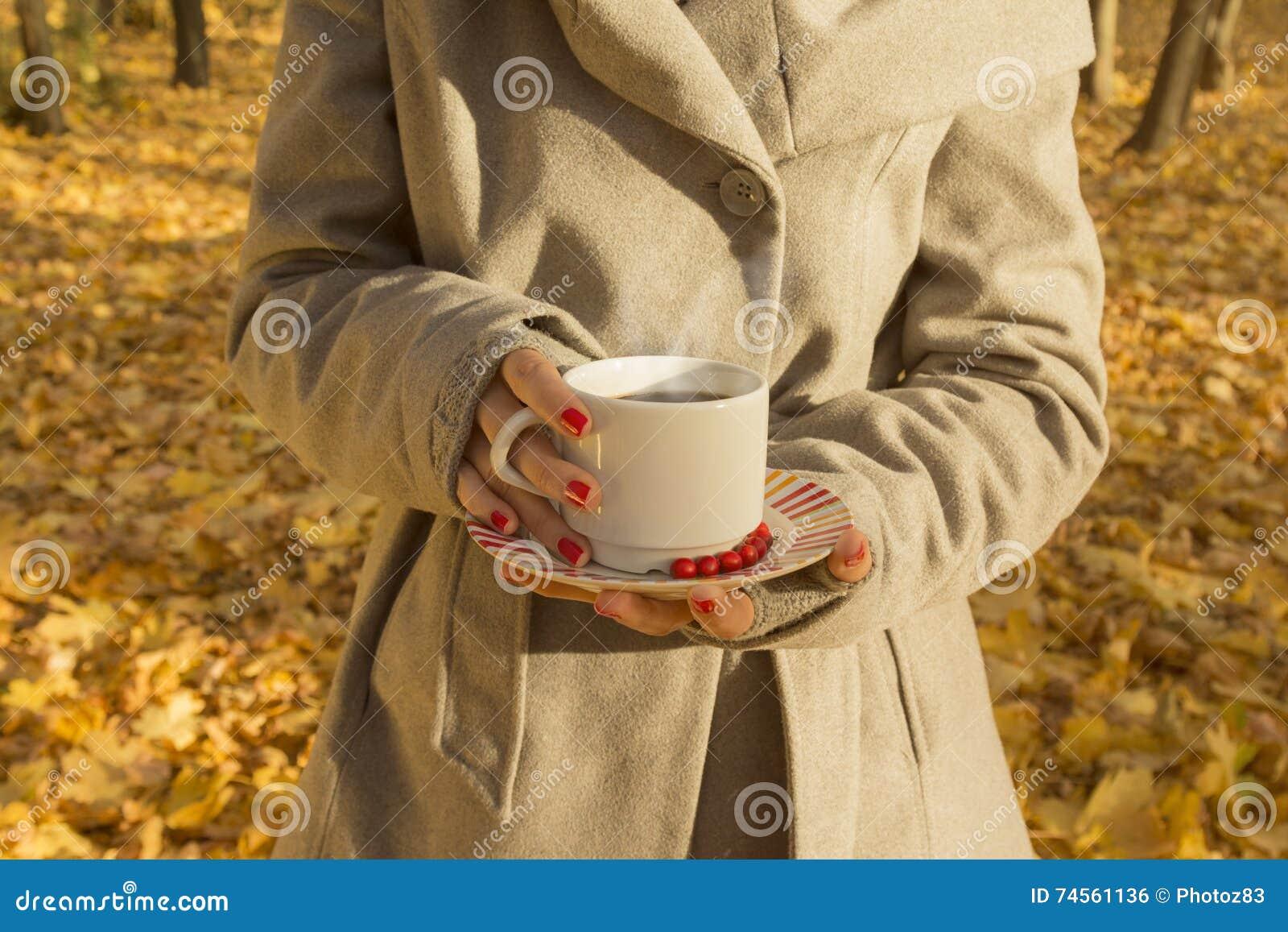 Fêmea que guarda um copo do café preto nas madeiras