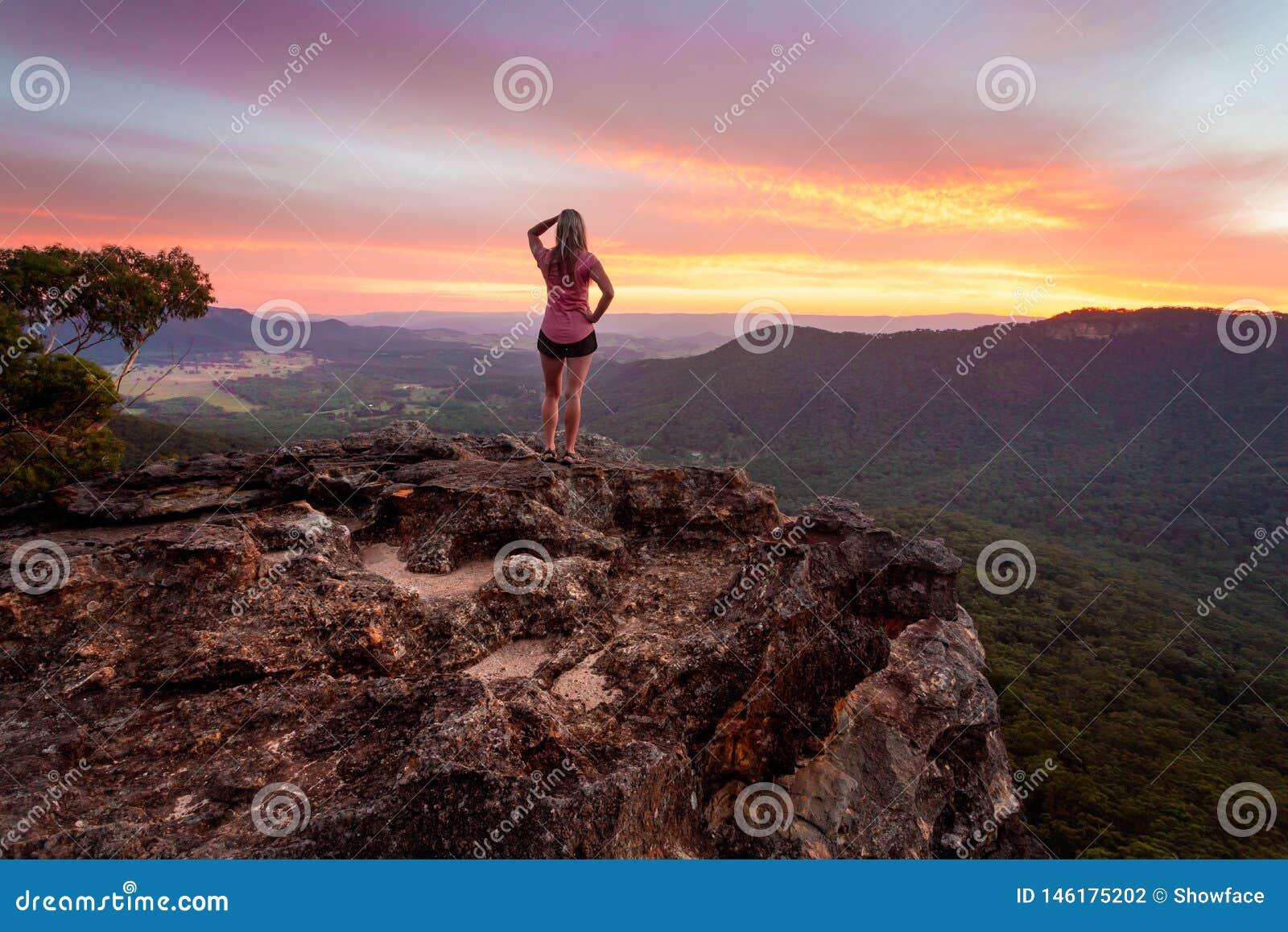 Fêmea que olha o por do sol após um dia longo que caminha em montanhas azuis