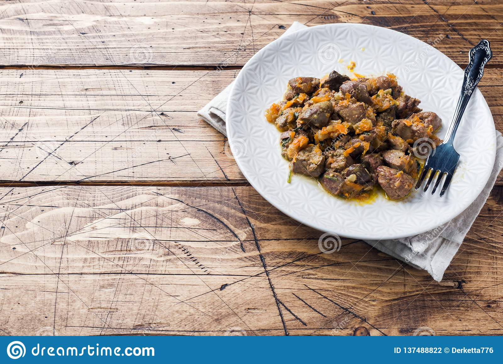 Fígado de galinha cozido com vegetais em uma placa Fundo de madeira