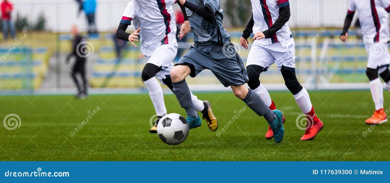 Fósforo de futebol júnior Jogo de futebol para jogadores da juventude Meninos que jogam o fósforo de futebol no passo de futebol