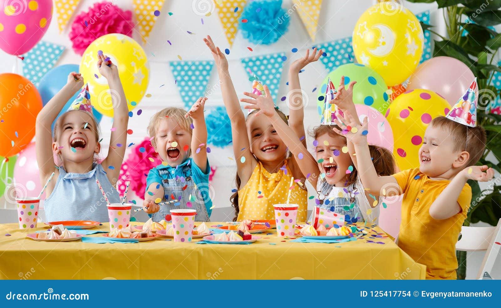 Födelsedag för barn` s lyckliga ungar med kakan