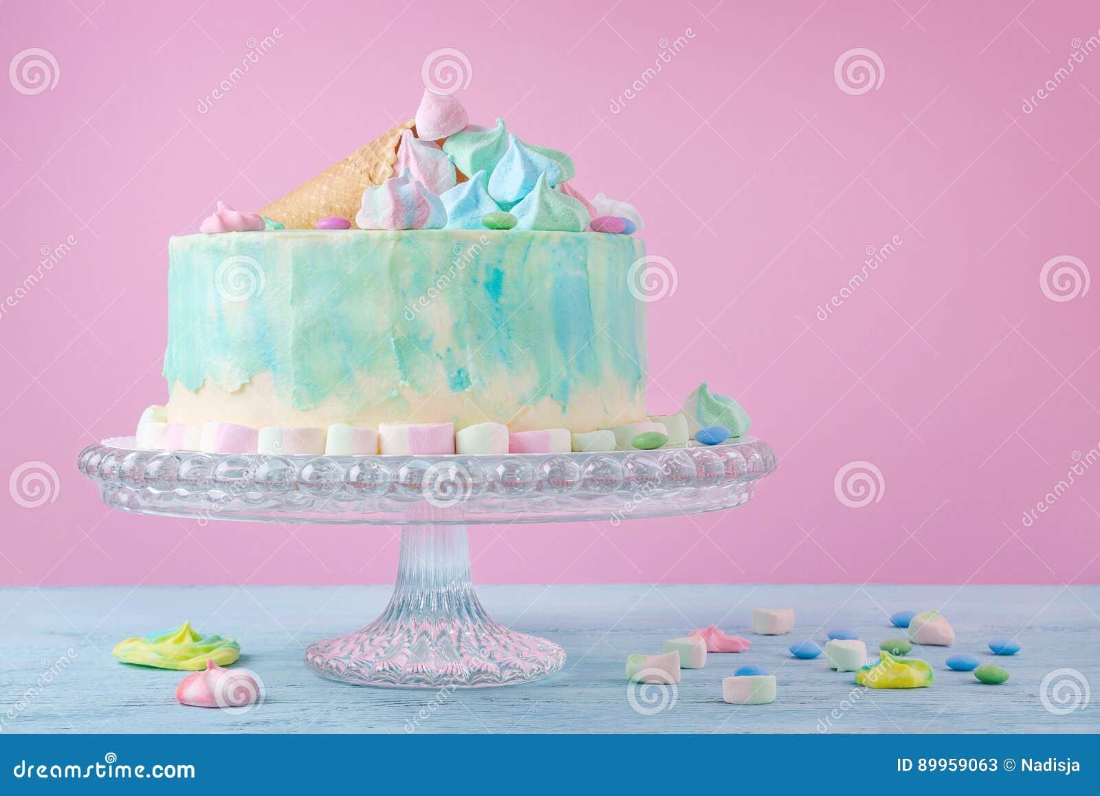 Födelsedagkaka i pastellfärgade färger, marshmallow och godisar på rosa bakgrund, selektiv fokus