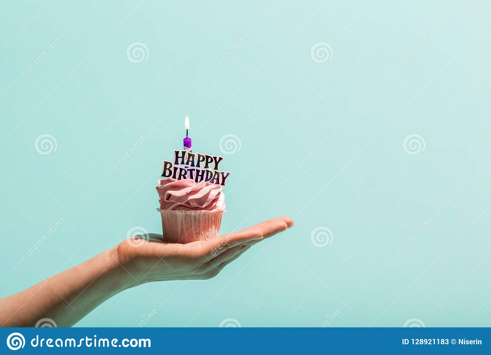 Födelsedagmuffin med stearinljuset rymde i hand för kvinna` s