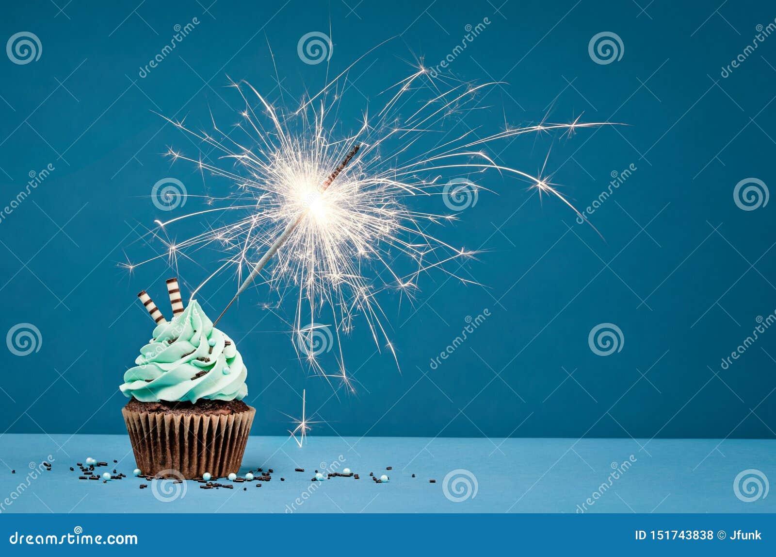 Födelsedagmuffin med tomteblosset på en blå bakgrund