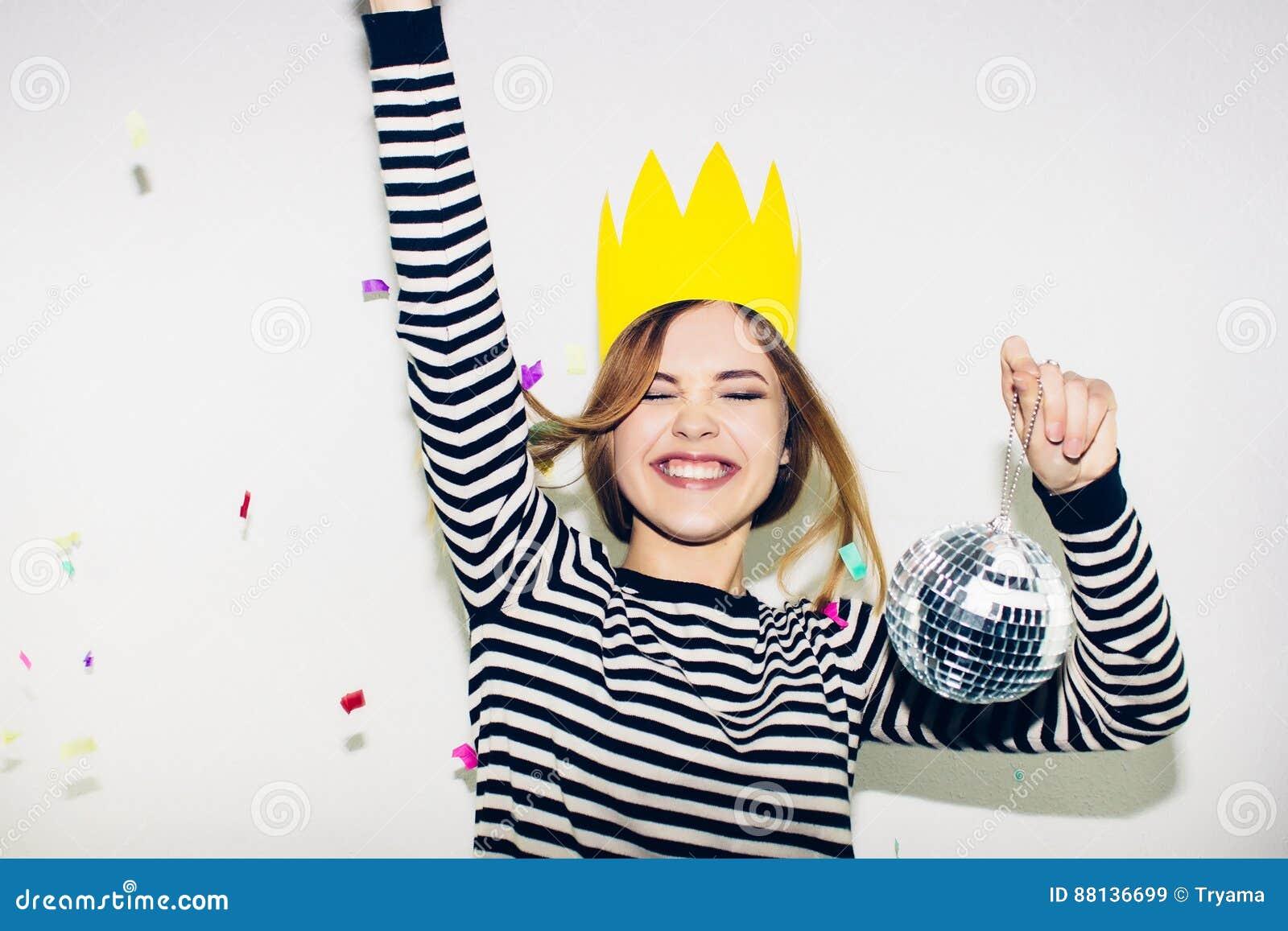 Födelsedagparti, karneval för nytt år Den unga le kvinnan på vit bakgrund som firar brightful händelse, bär avrivet