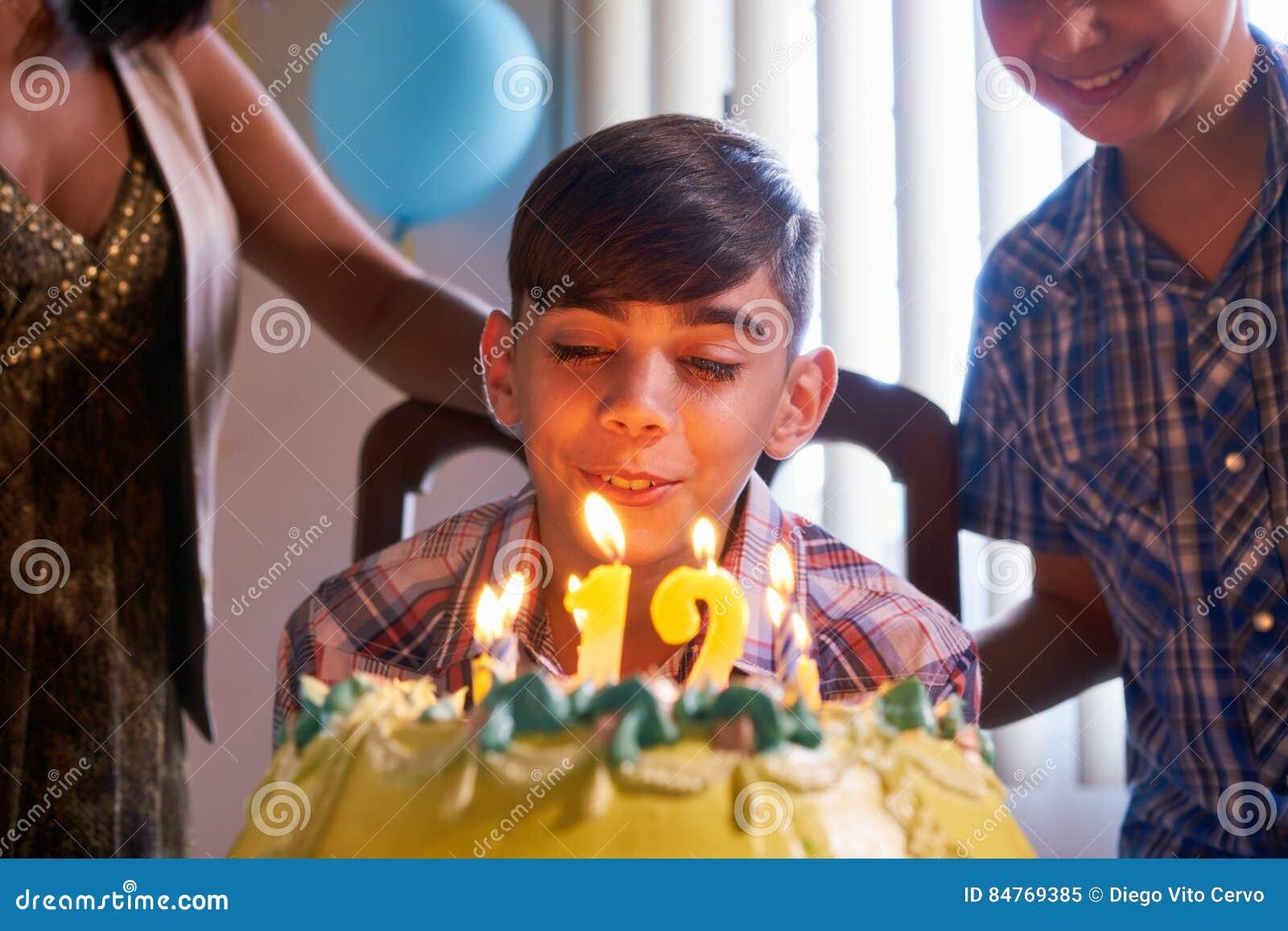 Födelsedagparti med den lyckliga Latinopojken som blåser stearinljus på kakan