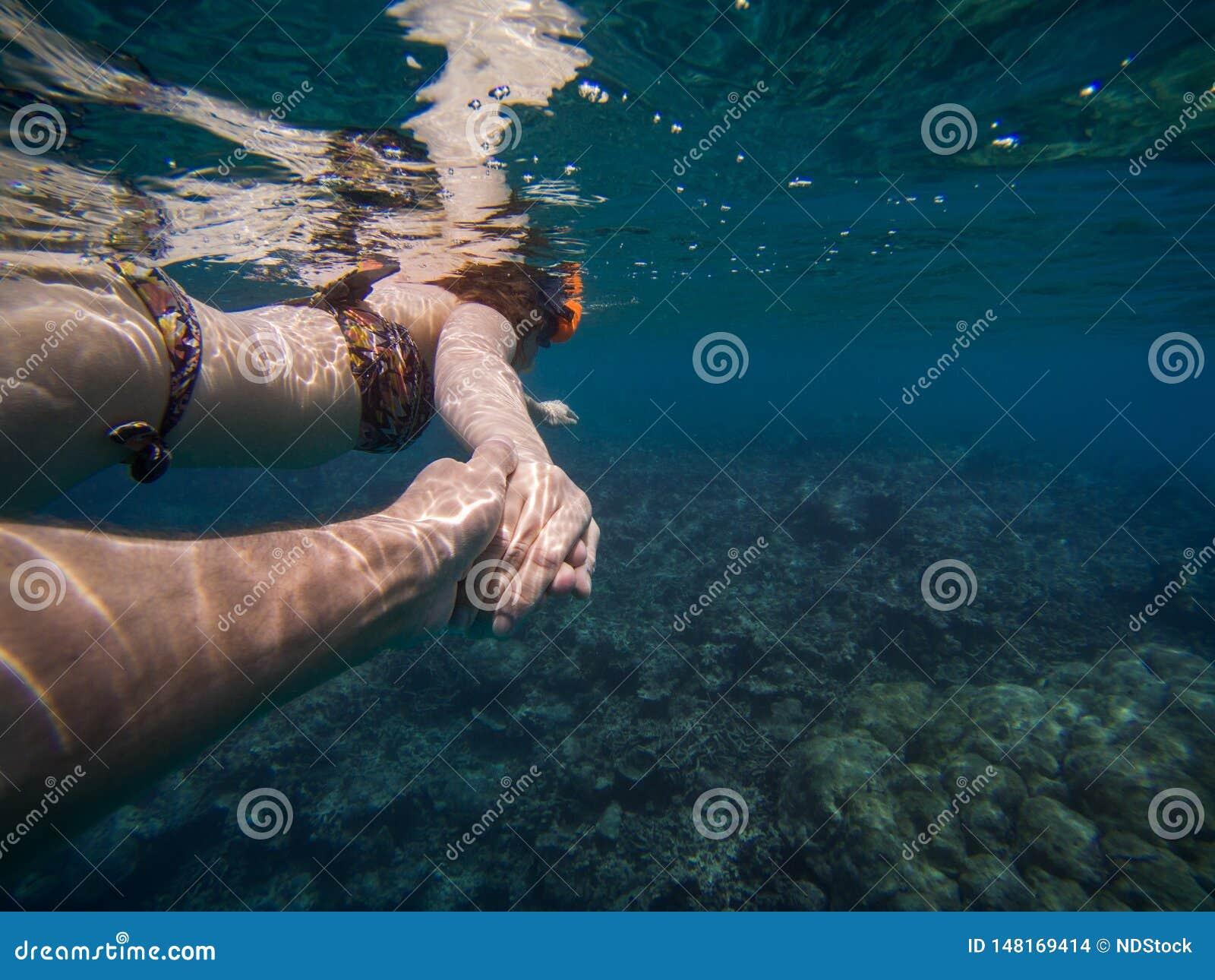 Följ mig begreppet av ett ungt par som snorklar i havet bl?tt klart vatten