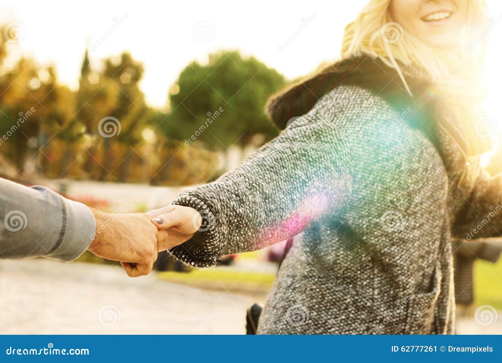 Följ mig - flickan som drar handen av en man