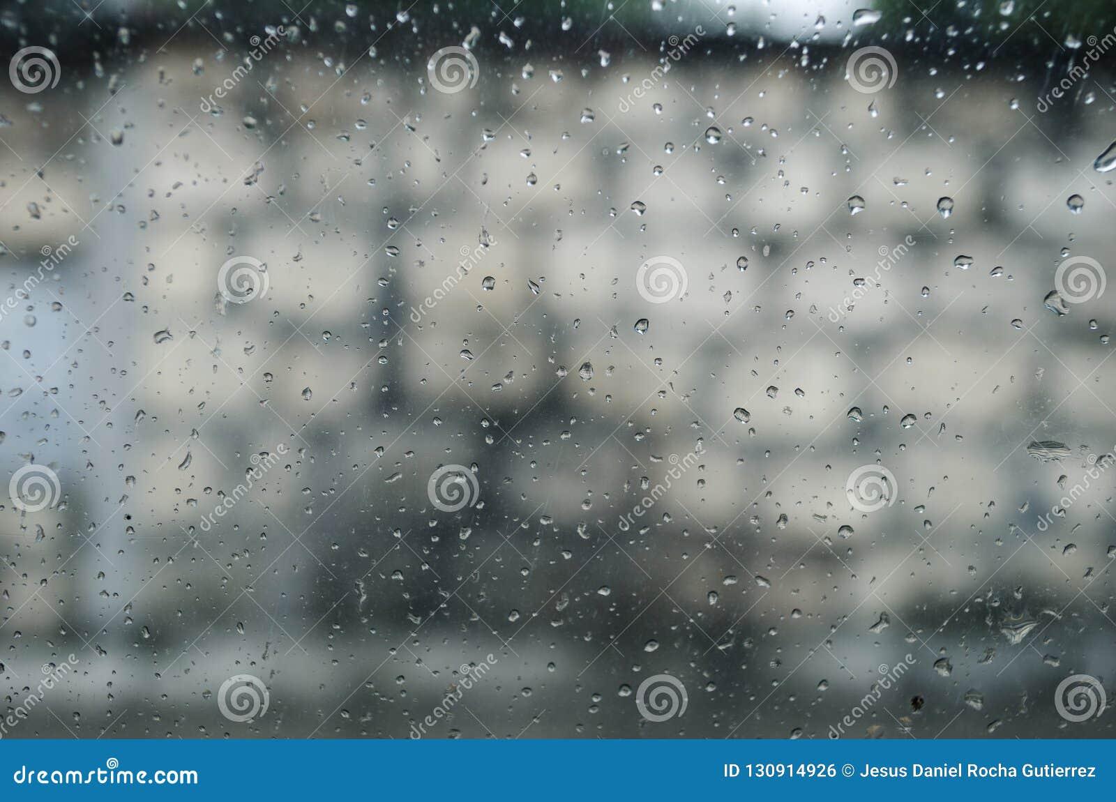Fönster i förgrunden av inre av en bil med droppar av vatten och en bakgrundsvägg med stora tegelstenar