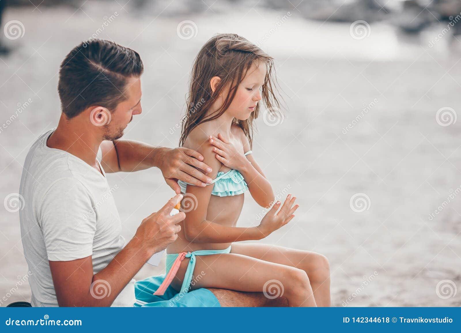 Förälder som applicerar solkräm till ungenäsan Stående av lttleflickan i suncream
