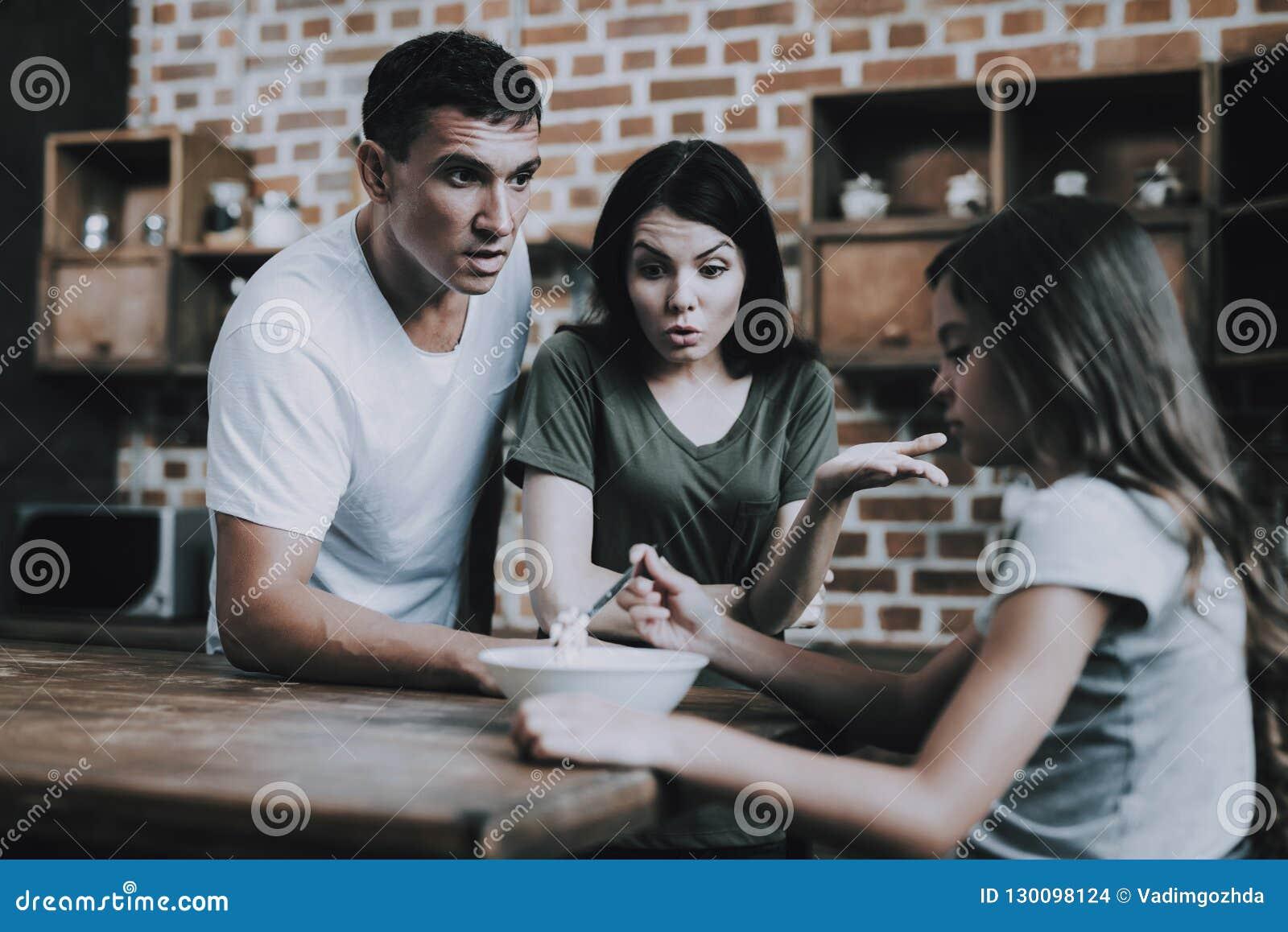 Föräldrar grälar på flickan som undviker att äta frukosten